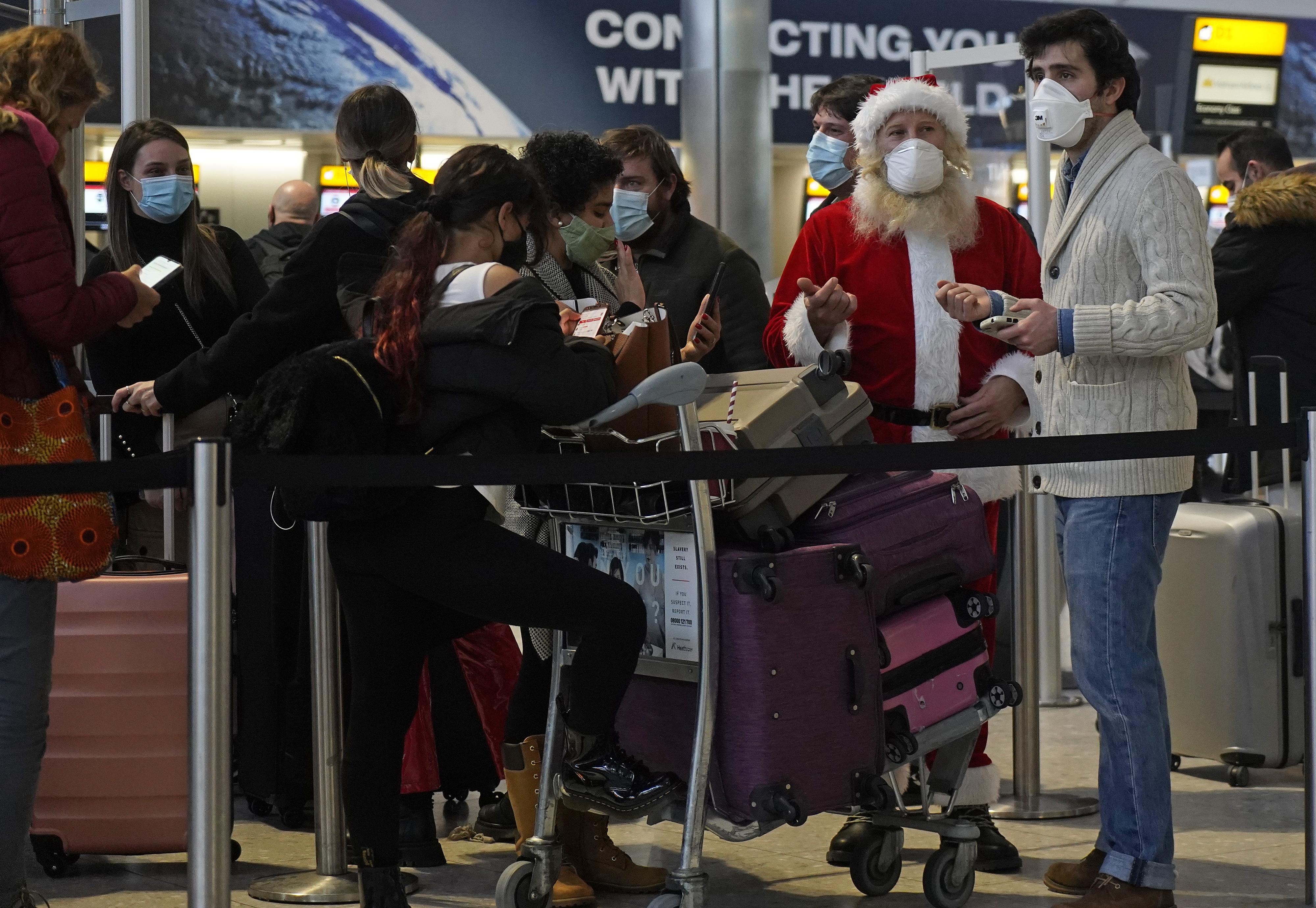 Pasajeros hacen cola con su equipaje en la sala de salidas de la Terminal 2 del aeropuerto de Heathrow en el oeste de Londres el 21 de diciembre de 2020.