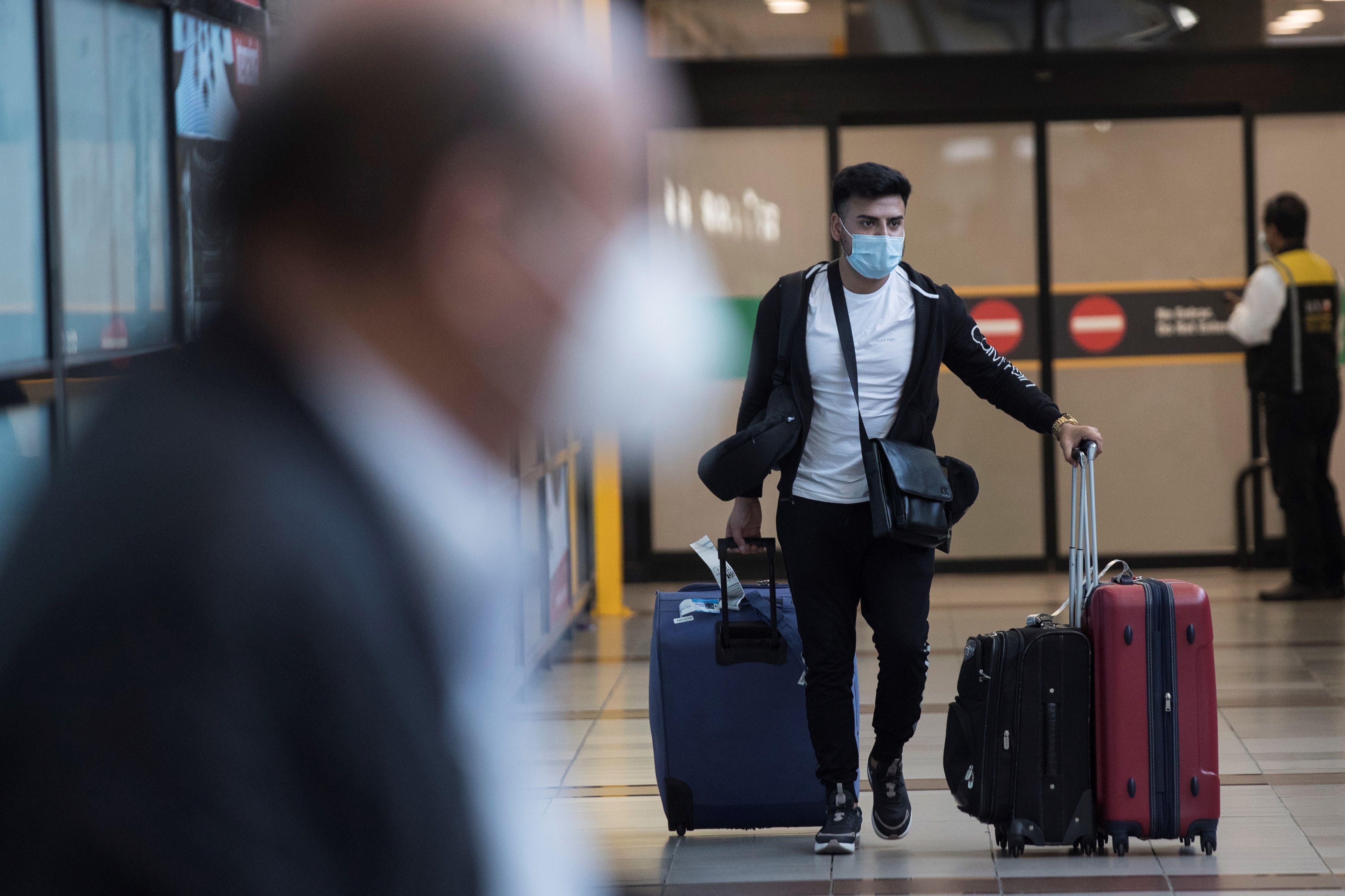 Viajeros con mascarillas llegan al aeropuerto Arturo Merino Benítez de Santiago, Chile.