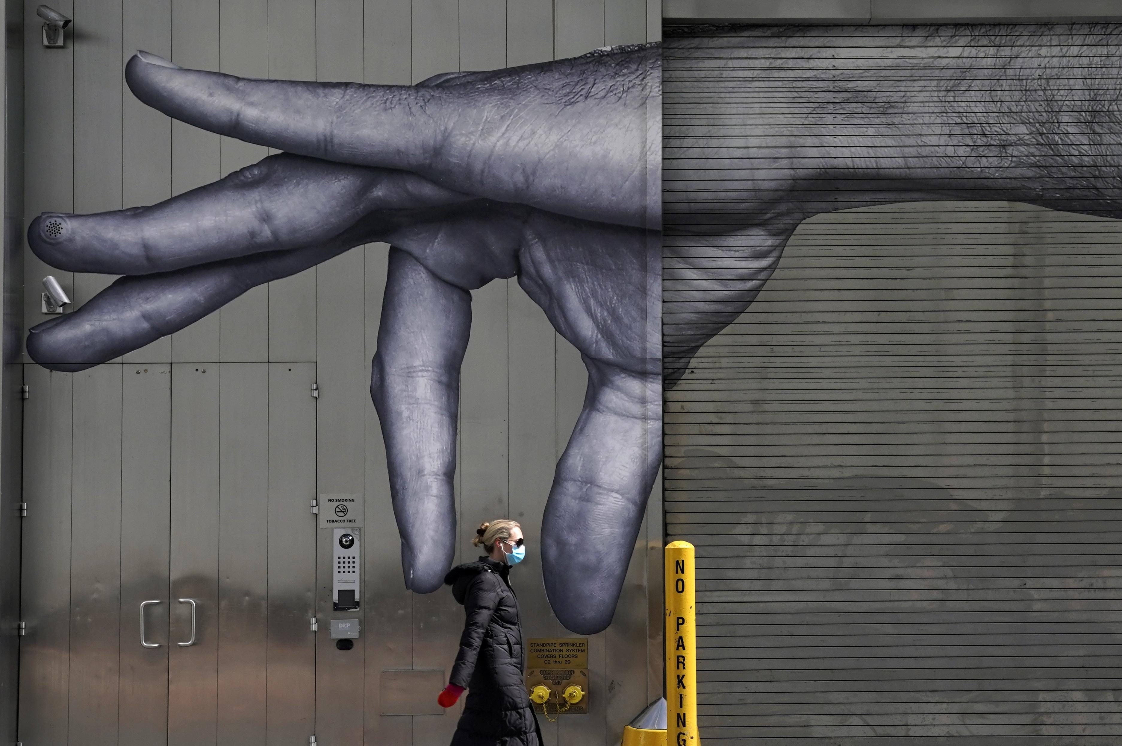Una mujer con tapabocas pasa junto a un mural en Midtown, Nueva York.