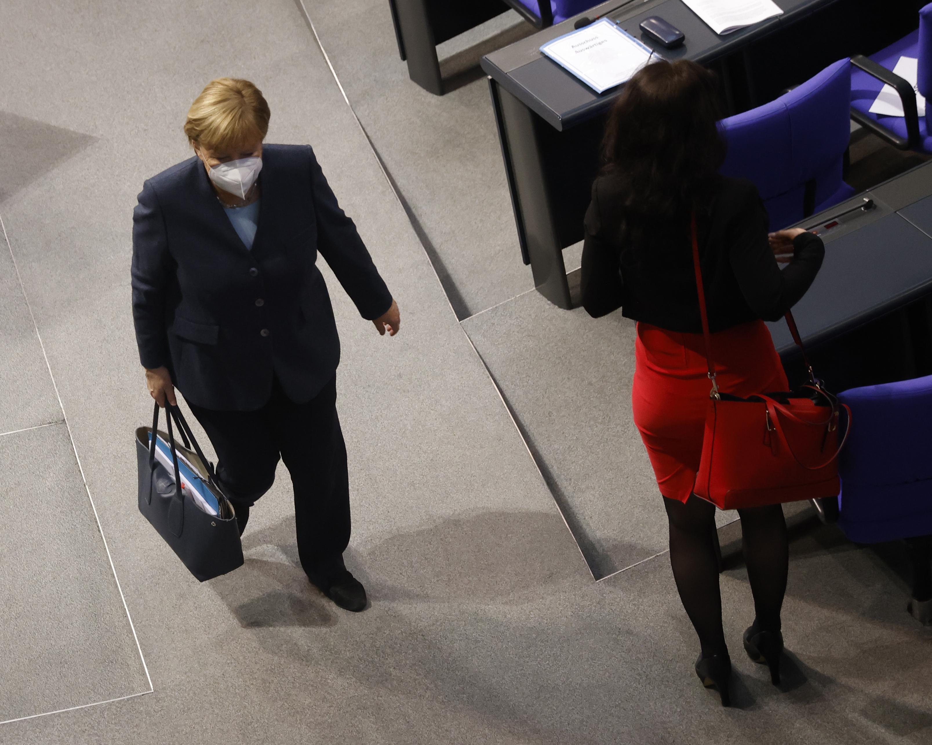 La canciller alemana, Angela Merkel (izq.), Se marcha después de una sesión del Bundestag (cámara baja del parlamento) en Berlín el 16 de diciembre de 2020, en medio de la pandemia del coronavirus Covid-19.