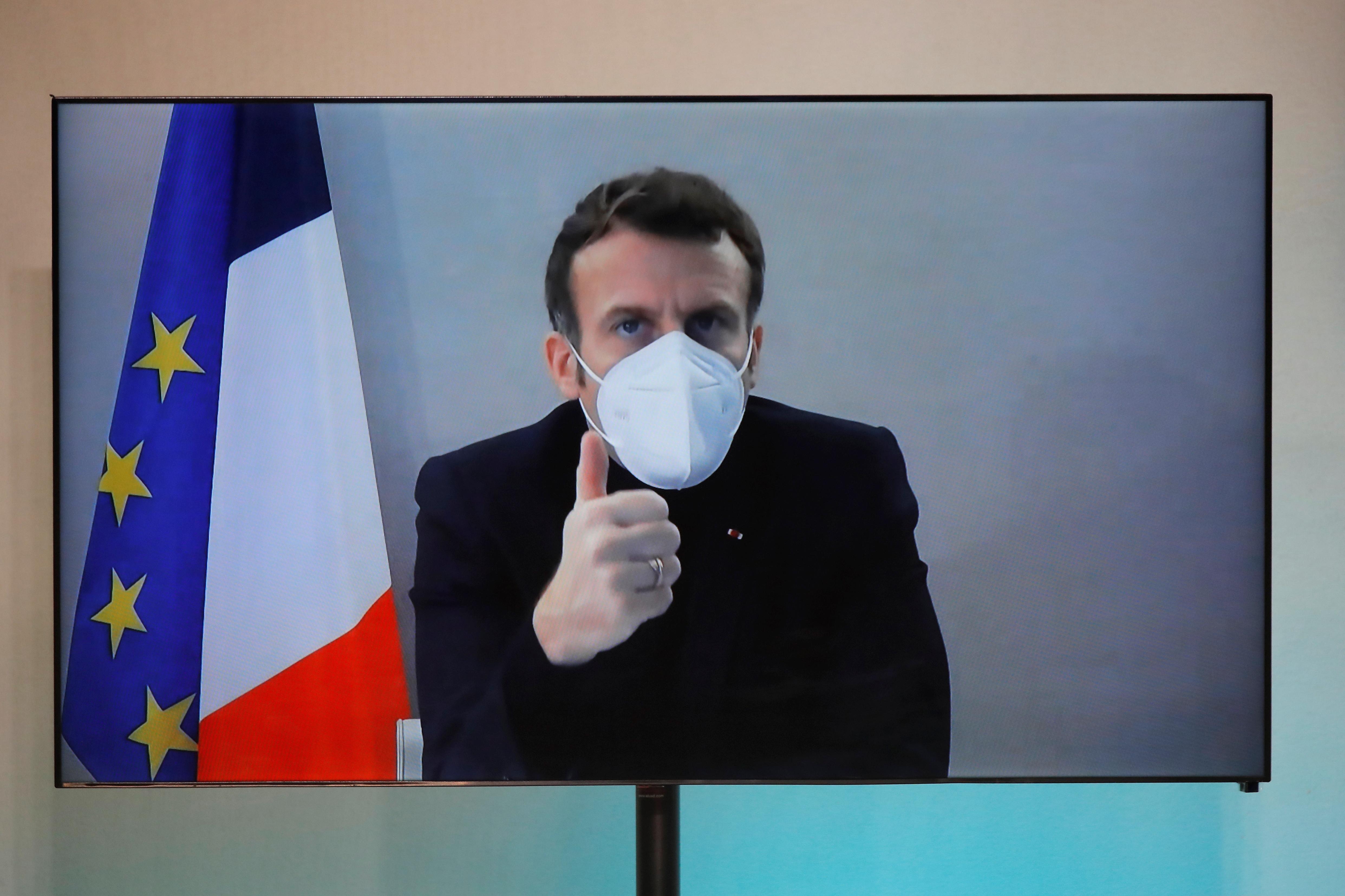 El presidente francés Emmanuel Macron, que dio positivo por la enfermedad del coronavirus (COVID-19), se ve en una pantalla mientras asiste por videoconferencia a una mesa redonda para la Conferencia Nacional Humanitaria (NHC)