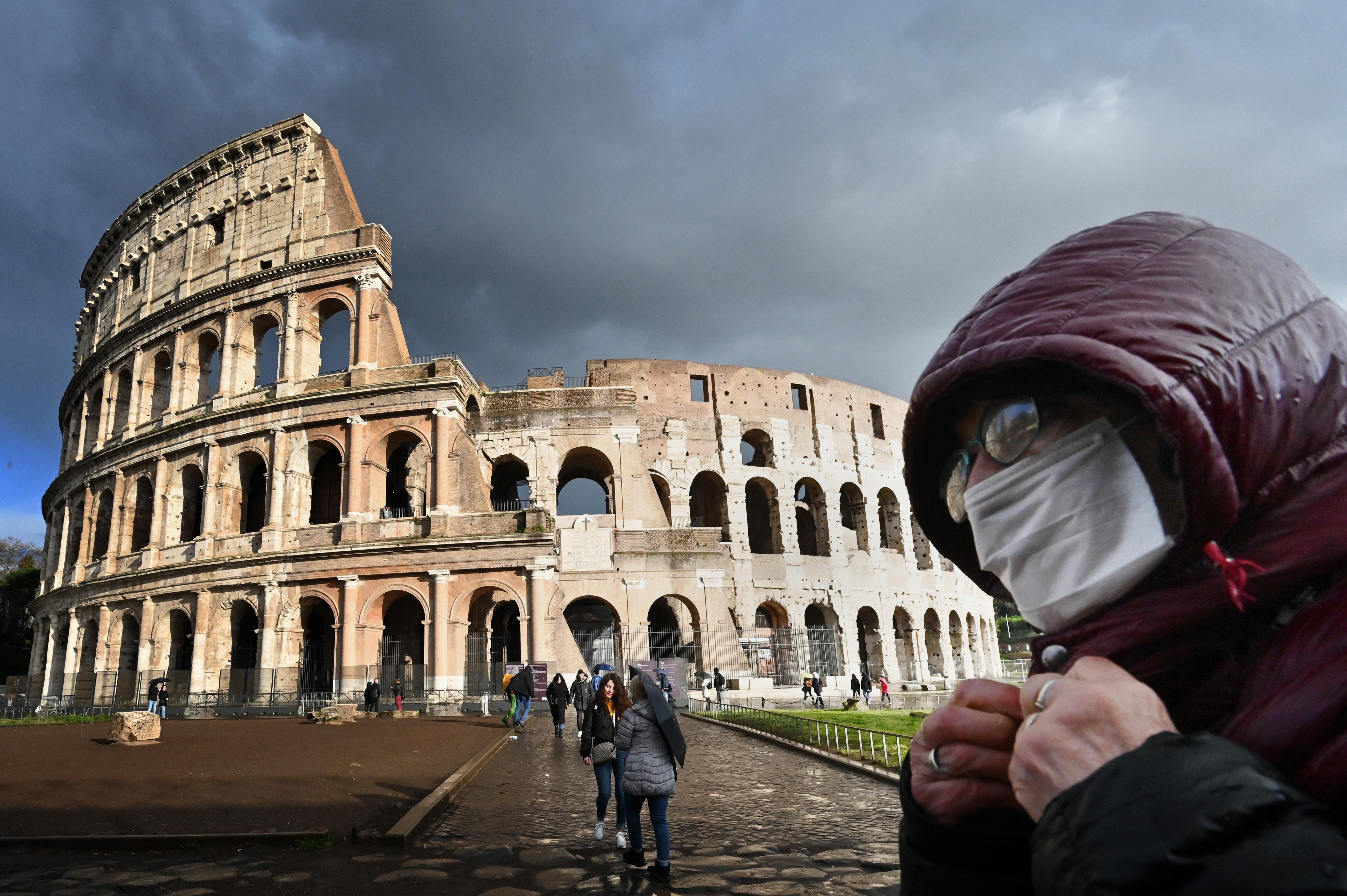 En esta foto de archivo tomada el 7 de marzo de 2020, un hombre con una máscara protectora pasa por el Coliseo en Roma en medio del temor a la epidemia de Covid-19.