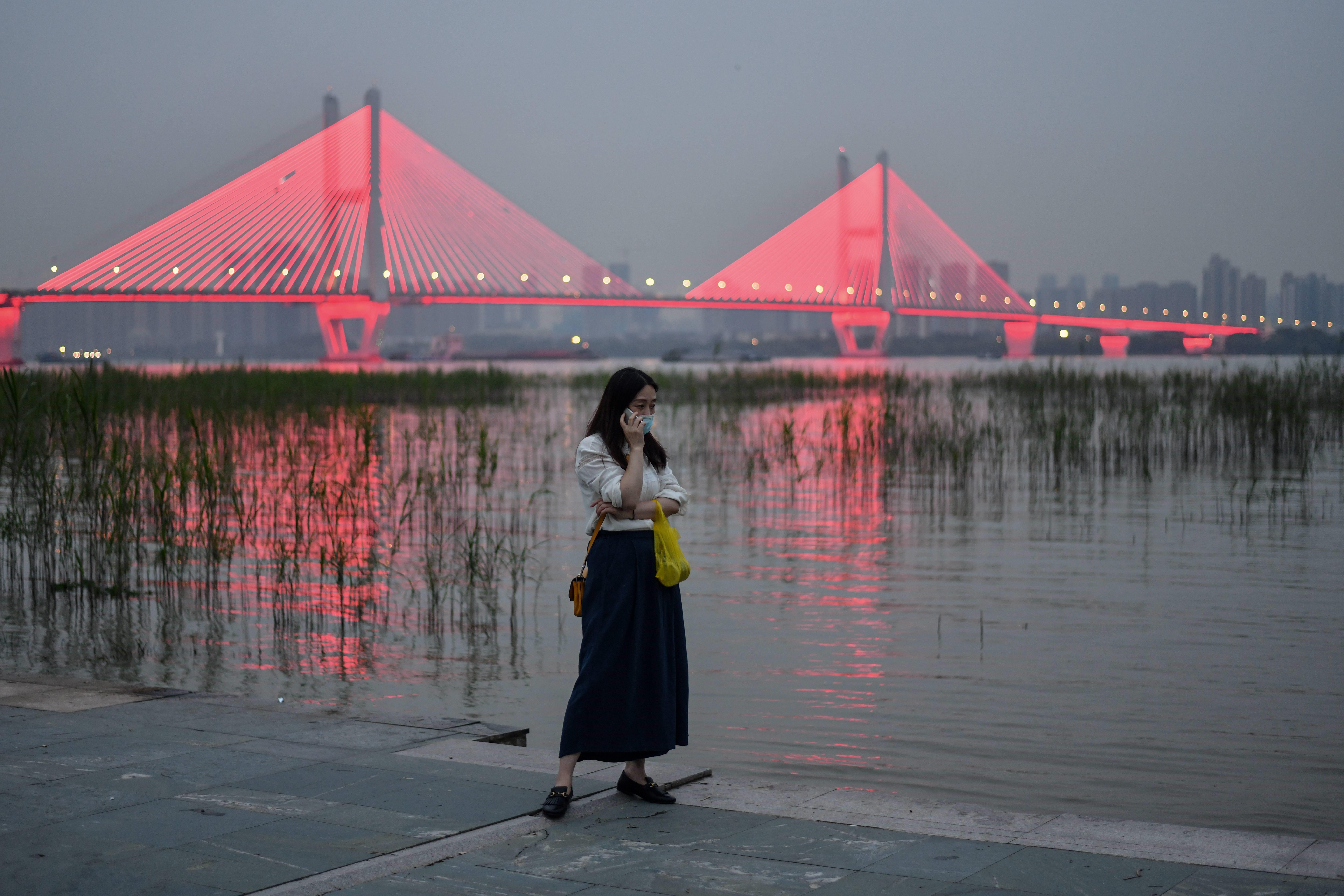 Una mujer con mascarilla como medida preventiva contra el coronavirus Covid-19 habla por teléfono junto al río Yangtze en Wuhan donde se originó la pandemia.