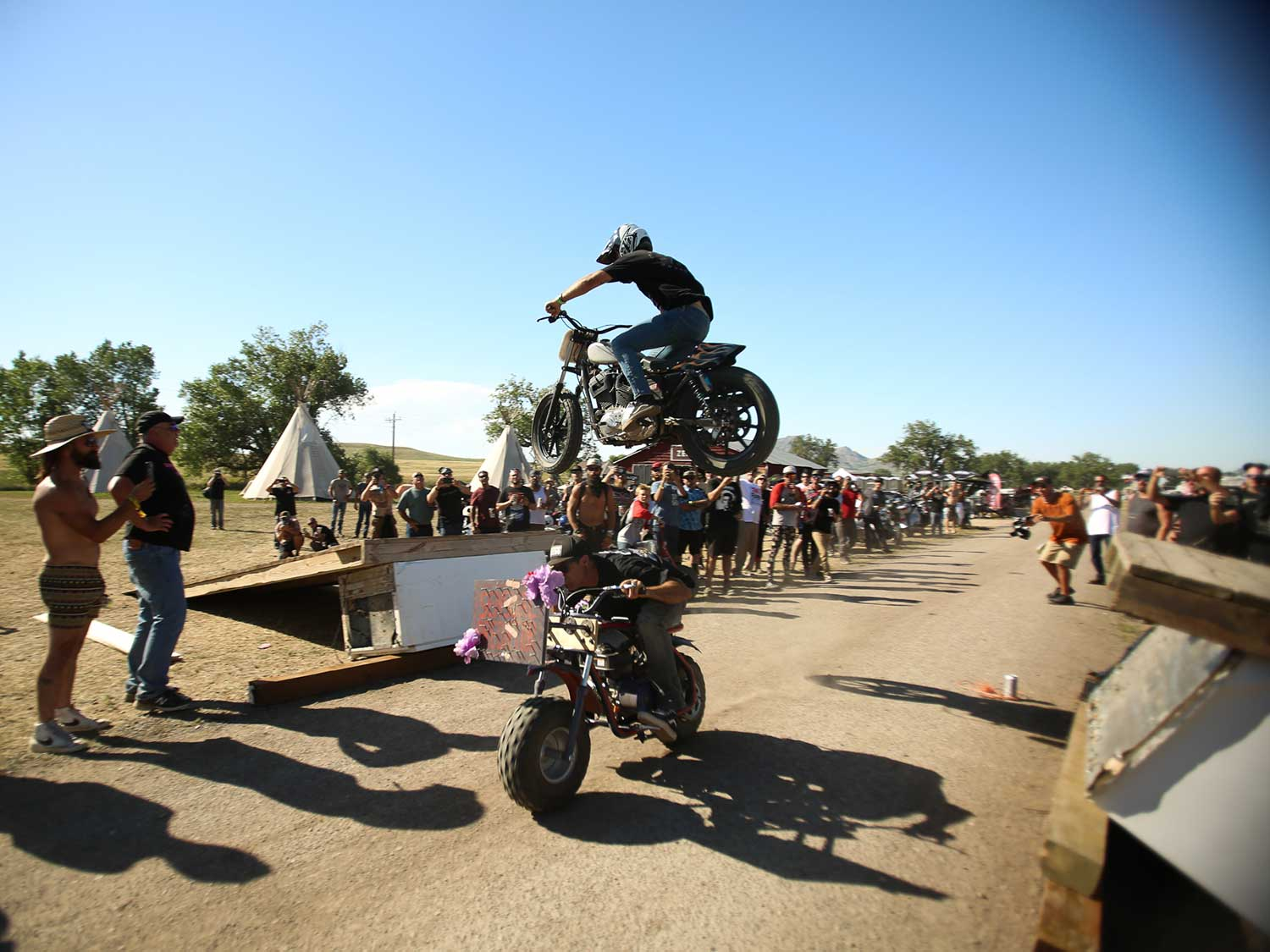 Sportster jumps over a rider on a minibike at Sturgis 2020