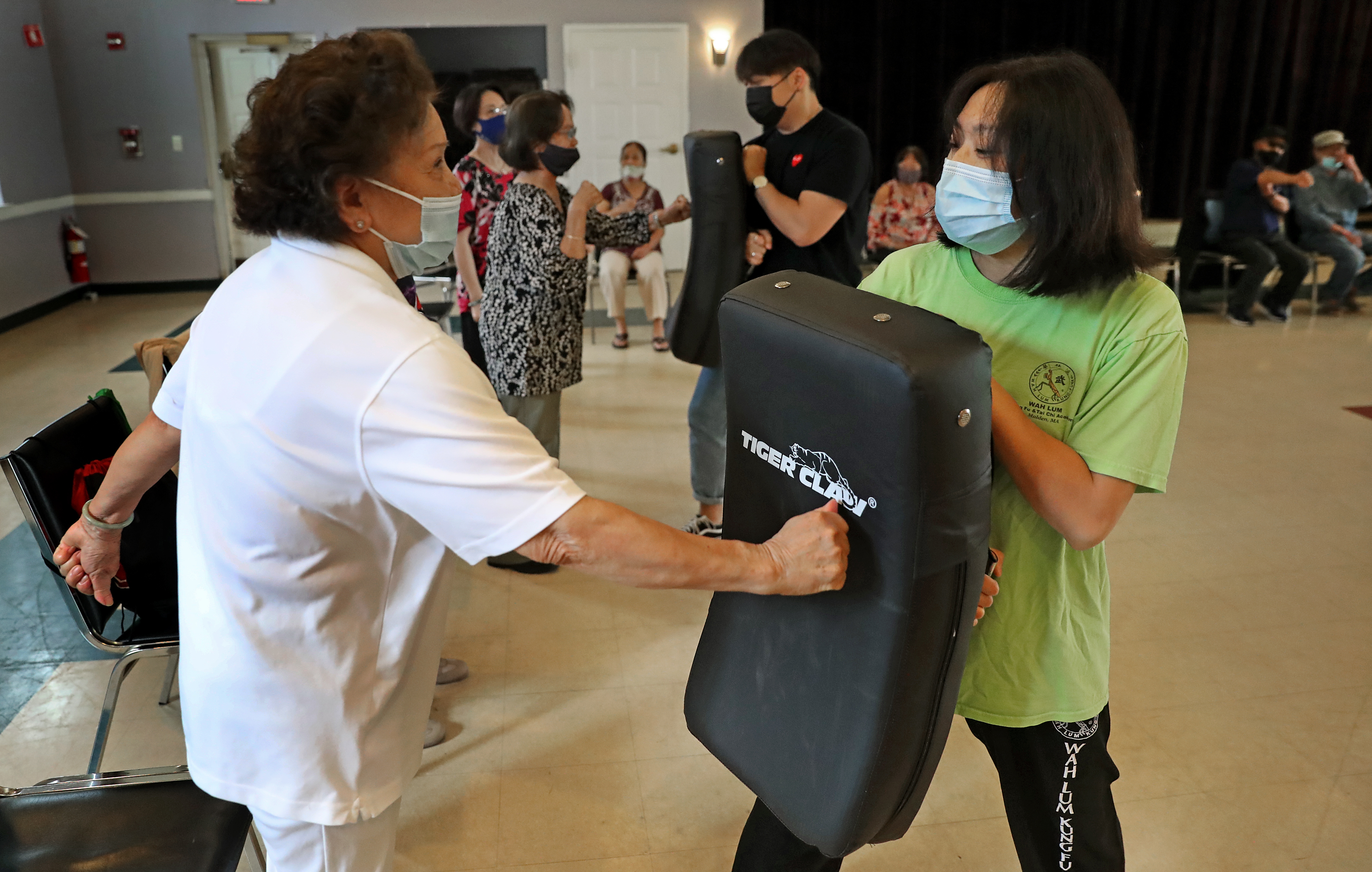 Linh Mat, 88, threw a punch during a demonstration on how to hit an attacker at VietAID's community center in Fields Corner, as instructor Mai Du (right) held the pad. Du is teaching seniors self-defense in response to a rash of assaults on older Asian Americans in many cities.