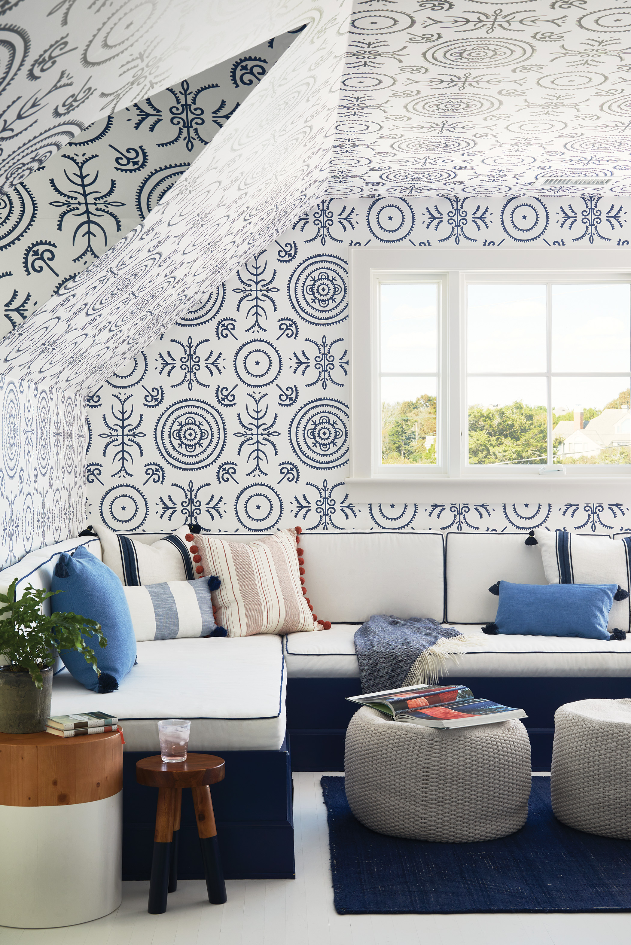 Studio Four NYC's Anna Spiro wallpaper covers the end of the attic, where a 15-foot U-channel wraps around a wall in front of the TV.