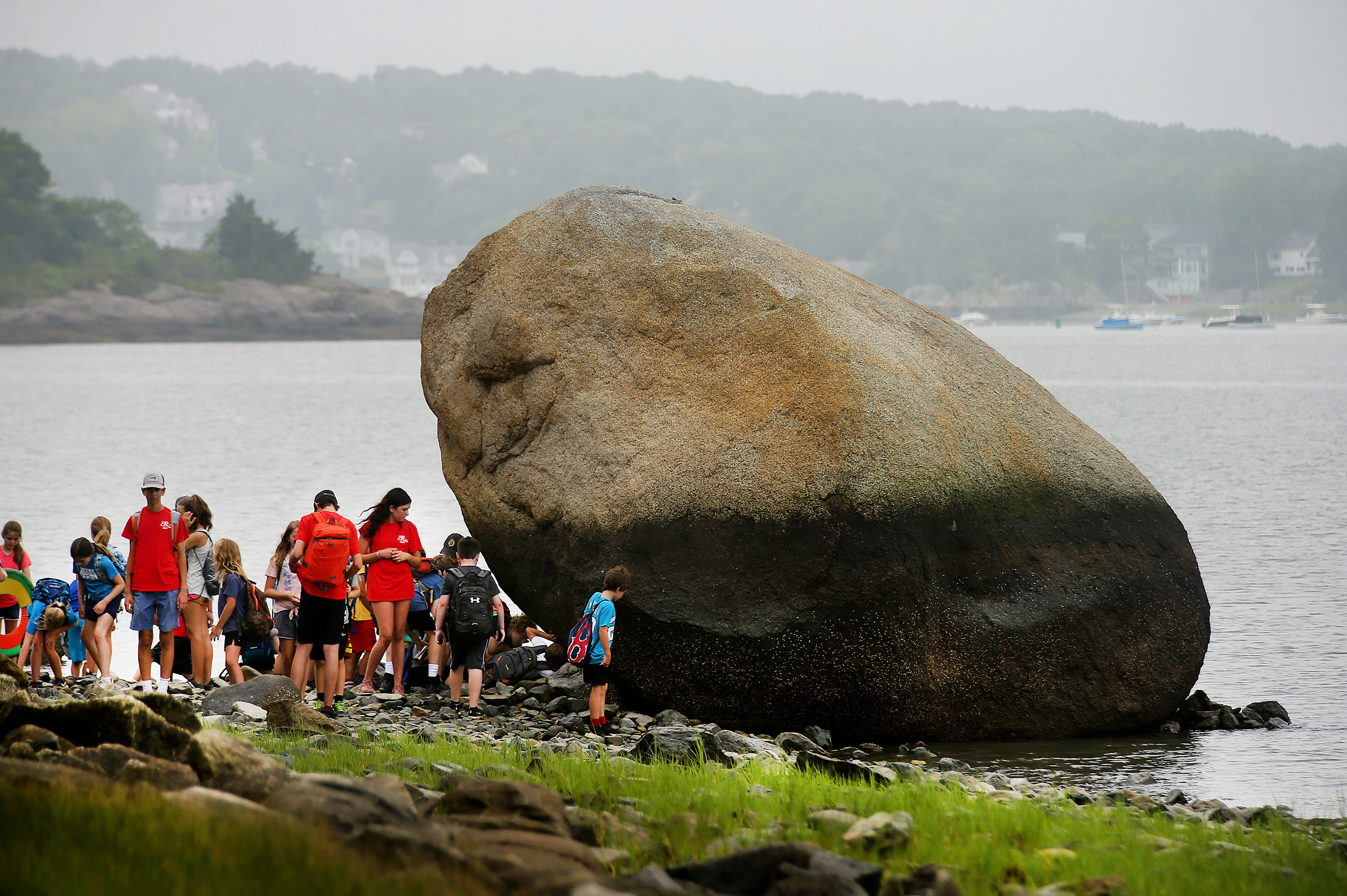 The kids from Hingham's Parks and Recreation Department stop to gaze at a huge boulder along the shore at World's End.