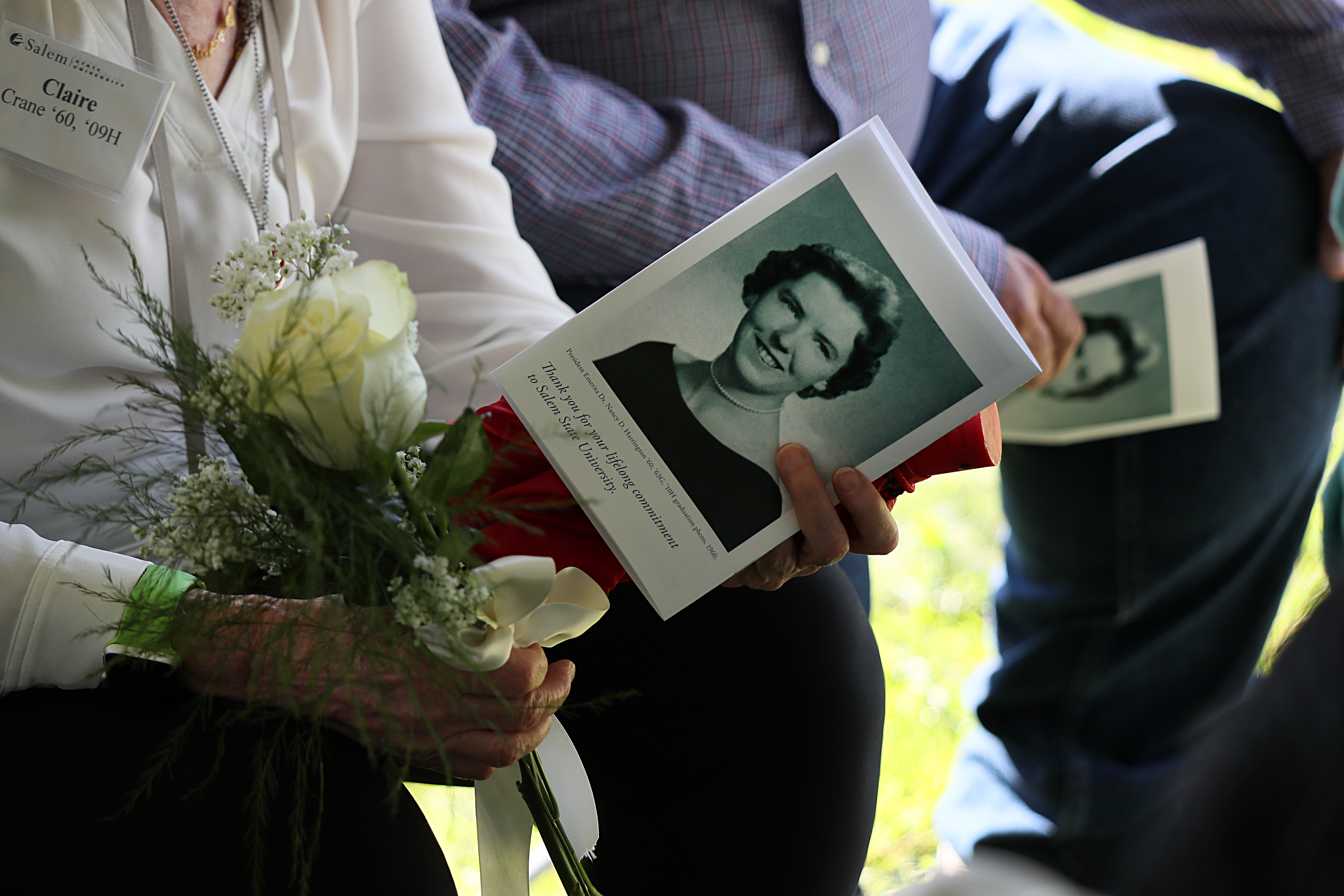 Members of the 1960 class received white roses in honor of their classmate, Nancy D. Harrington, at the ceremony on Friday.  Suzanne Kreiter / Globe staff