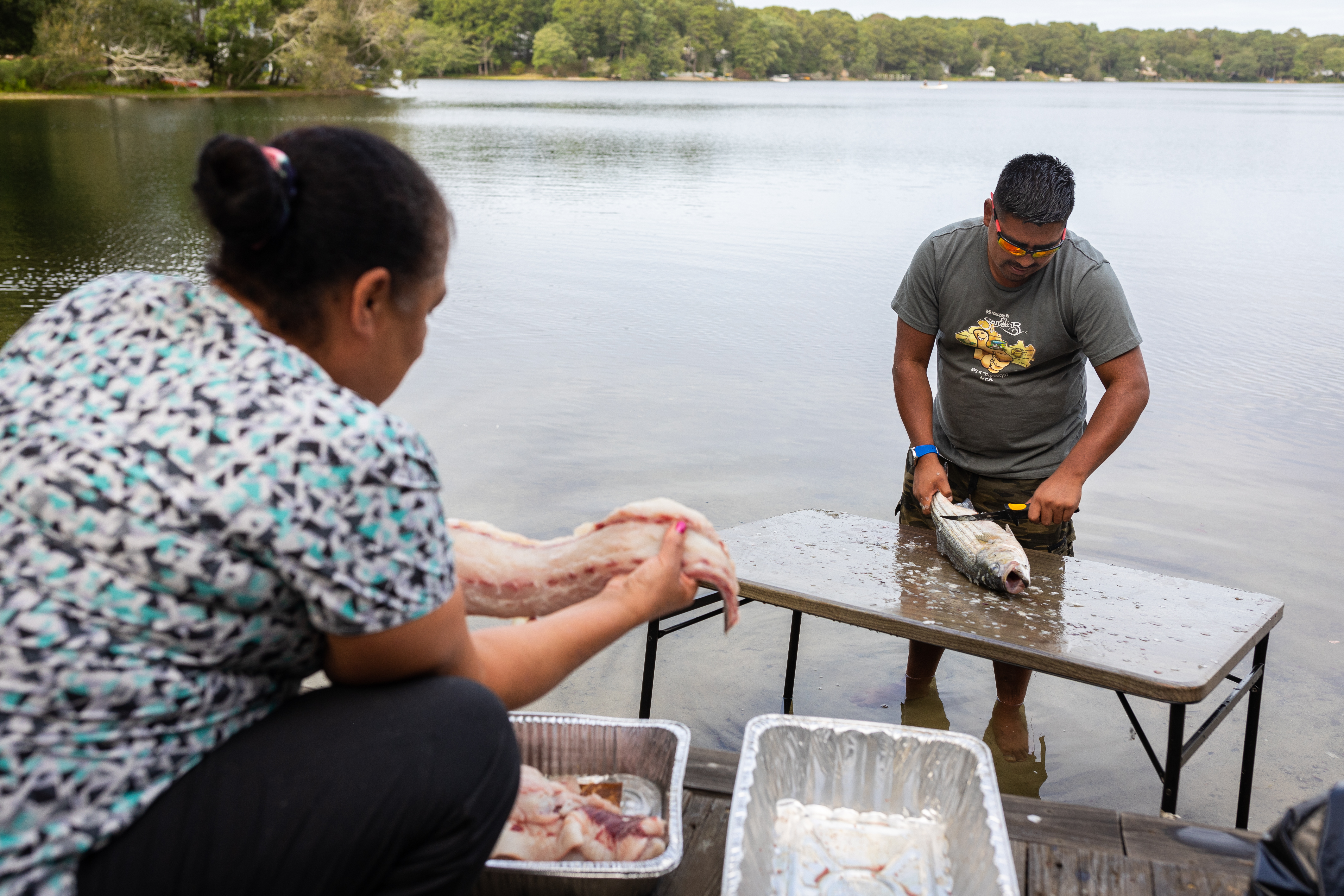 Darwin González descales a freshly caught striped bass as Delscena Hicks, a member of the Mashpee Wampanoag Tribe, picks up a striped bass filet in Centerville.