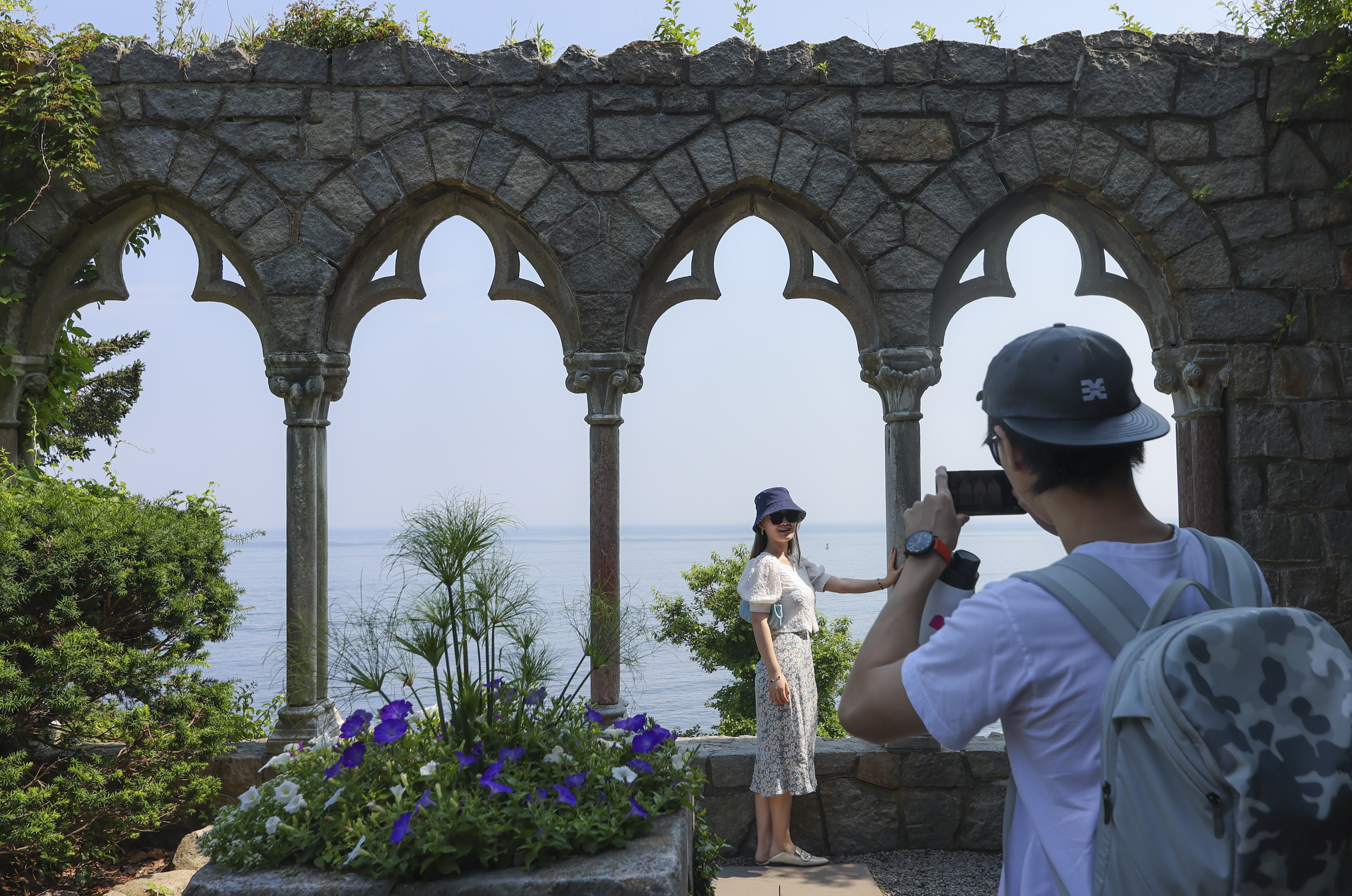 Ante Bing photographs his friend Mary Bai, both Boston residents, in front of 12th and 13th century Italian arches in front of the Hammond Castle Museum in Gloucester.
