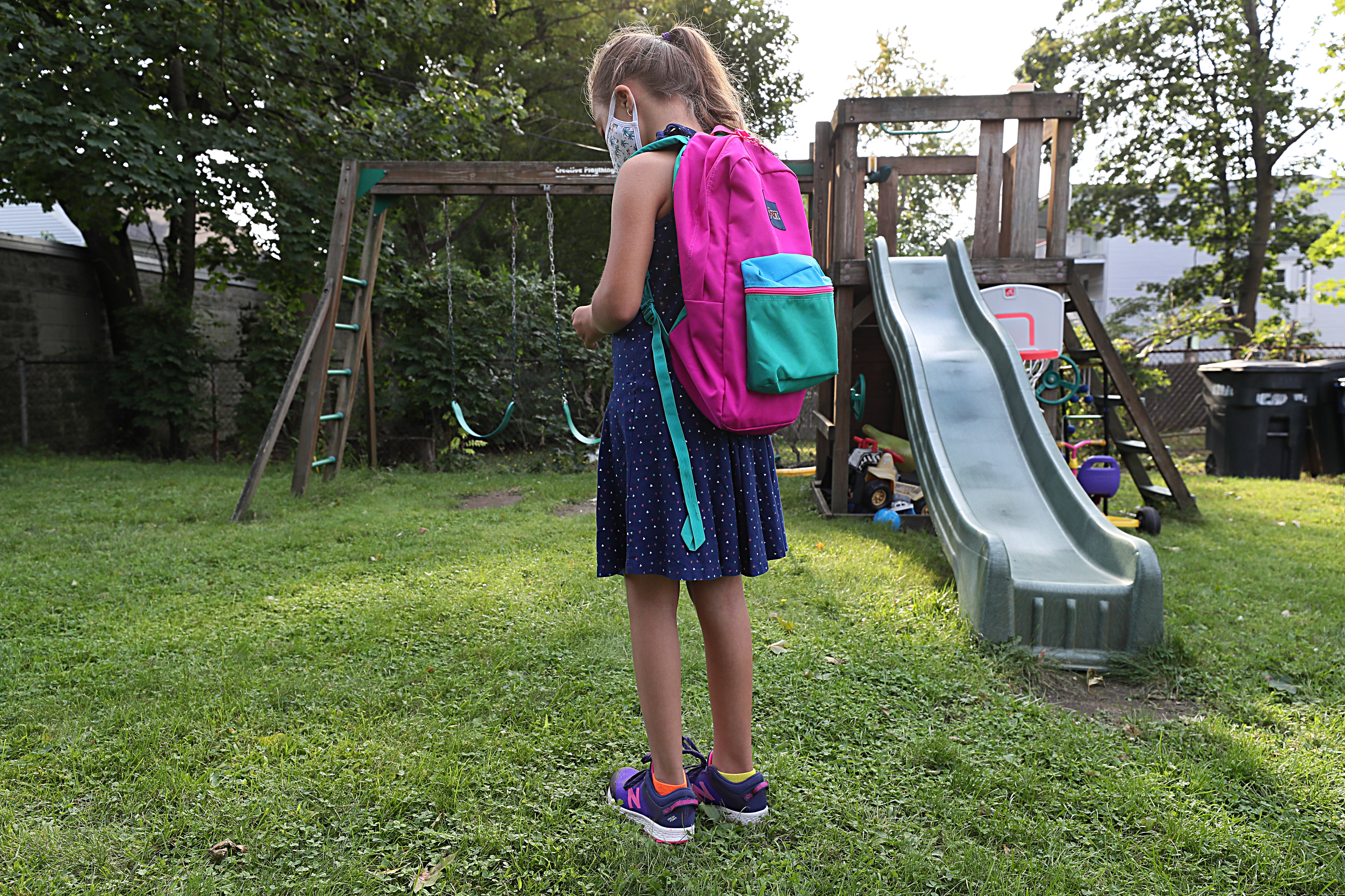 Lulu, 9, wears her back-to-school backpack in her backyard, but not yet to her school.