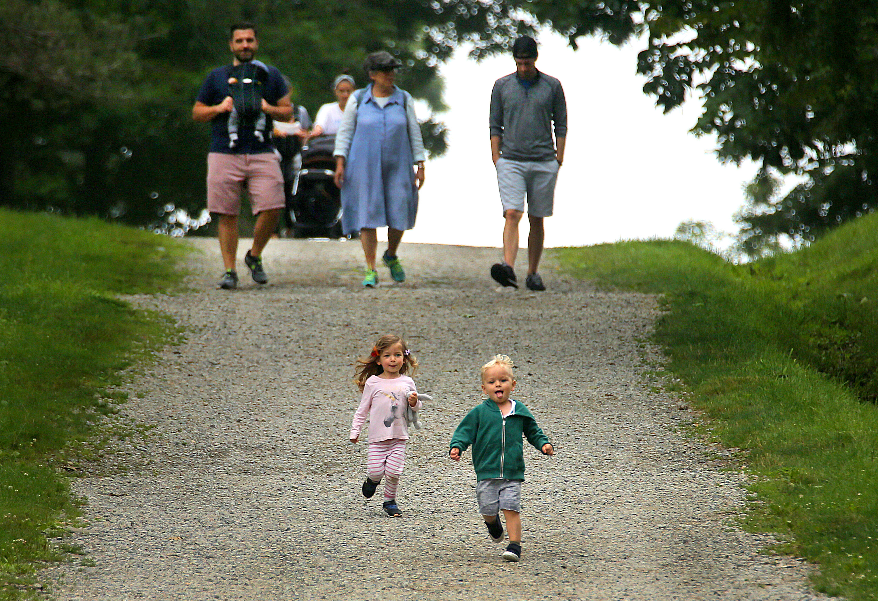 Maya Allen (left) and her cousin Max Wolff, both 2 1/2 from Montclair, NJ, run down a hill past their families.
