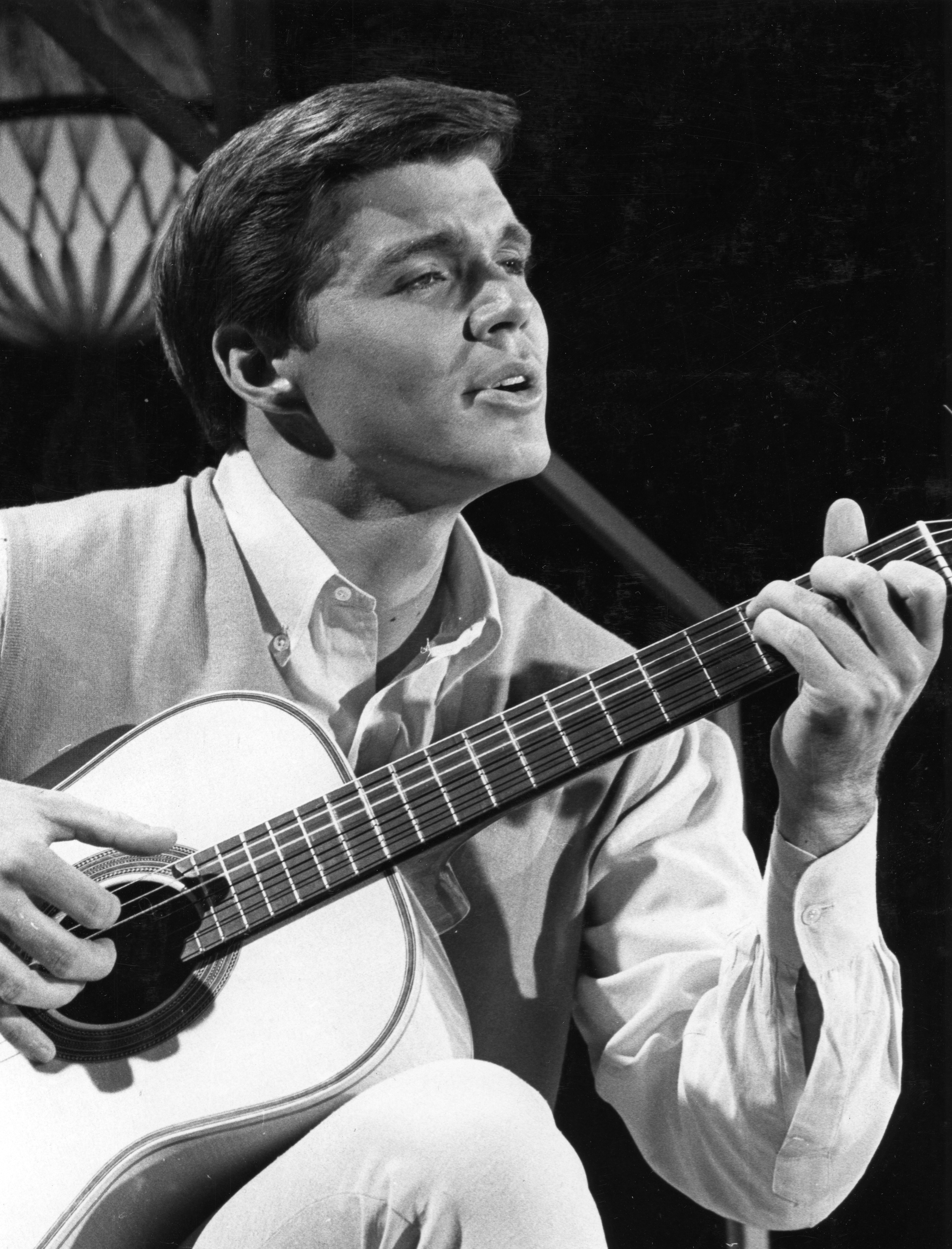 John Davidson in 1966. Here is the original caption of this photo: The versatile talent of 24-year-old John Davidson, shown with his guitar in Hollywood, came out after realizing, while studying for the ministry, that his appeal was in. much in speaking to an audience.  (