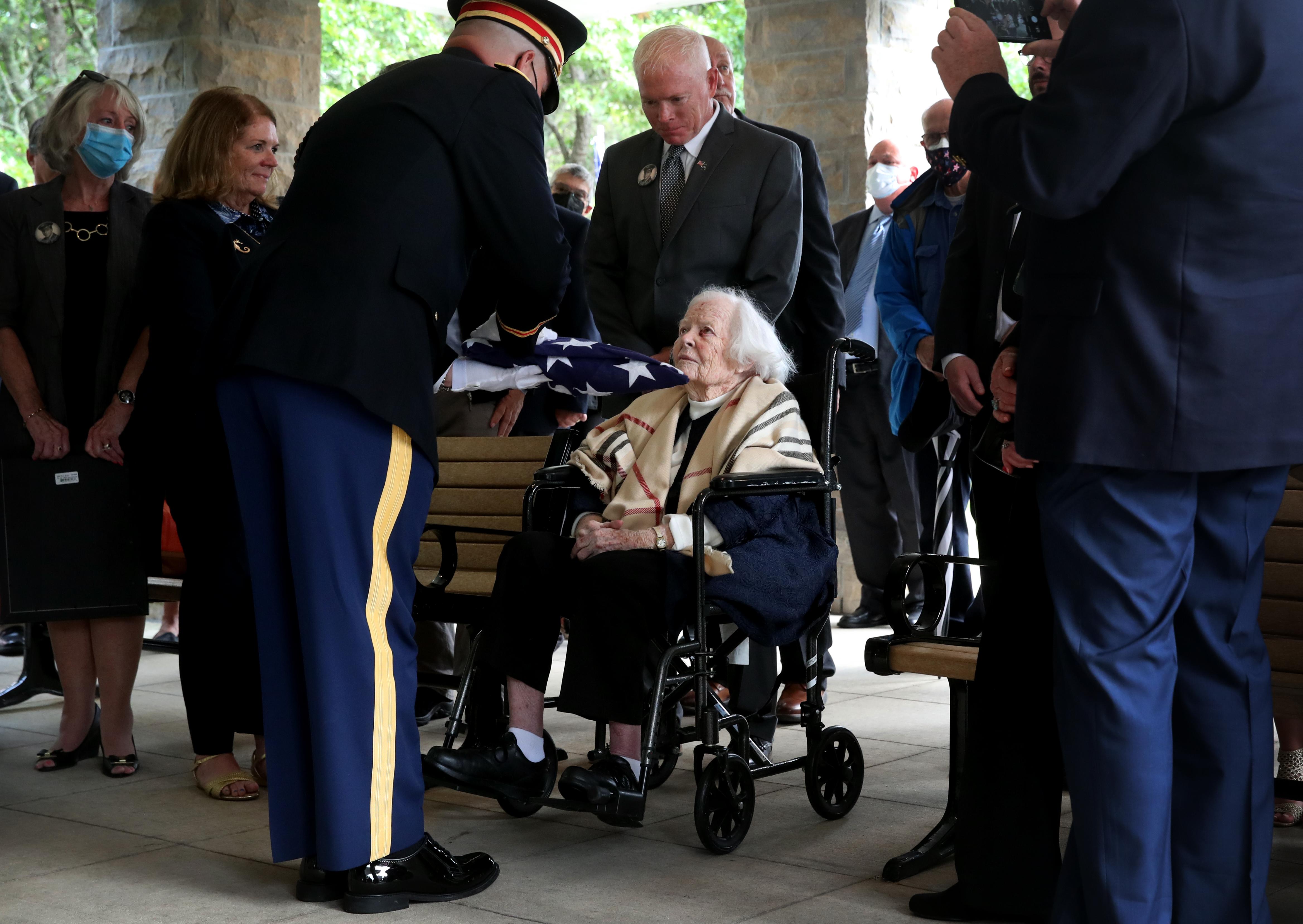 엘렌 오 칸 레드 게이트는 2021 년 9 월 17 일 메사추세츠 본 매사추세츠 국립 묘지에서 처남 인 토마스 J. 레드 게이트에 봉사하고있을 때 미국 국기를 제시했습니다.
