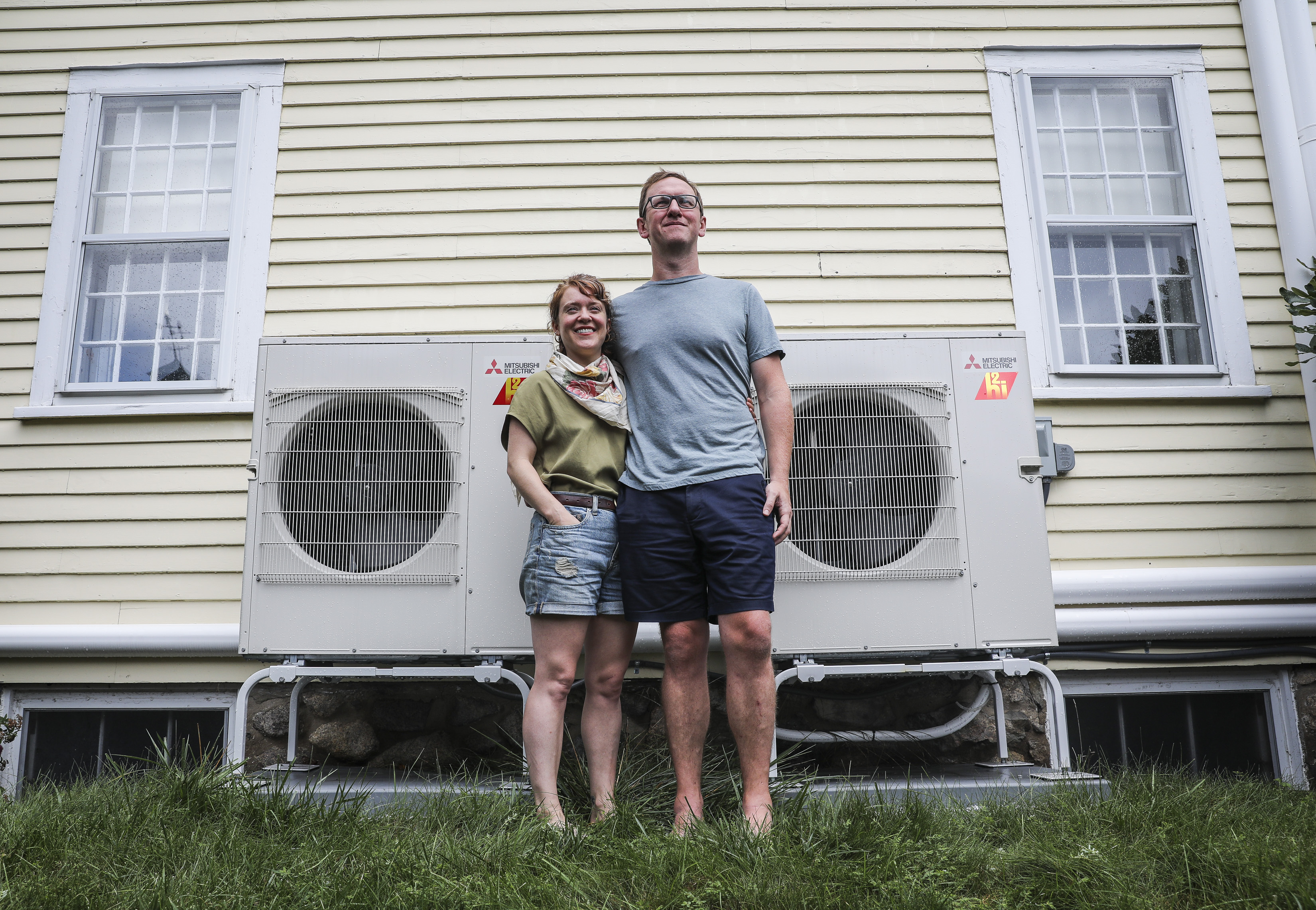 Ben Butterworth and his wife, Olivia Cerf, stood by the heat pumps they had installed at their Melrose home. Butterworth said that out the five contractors he spoke with, only one was comfortable fully converting his oil-burning heating system to heat pumps.