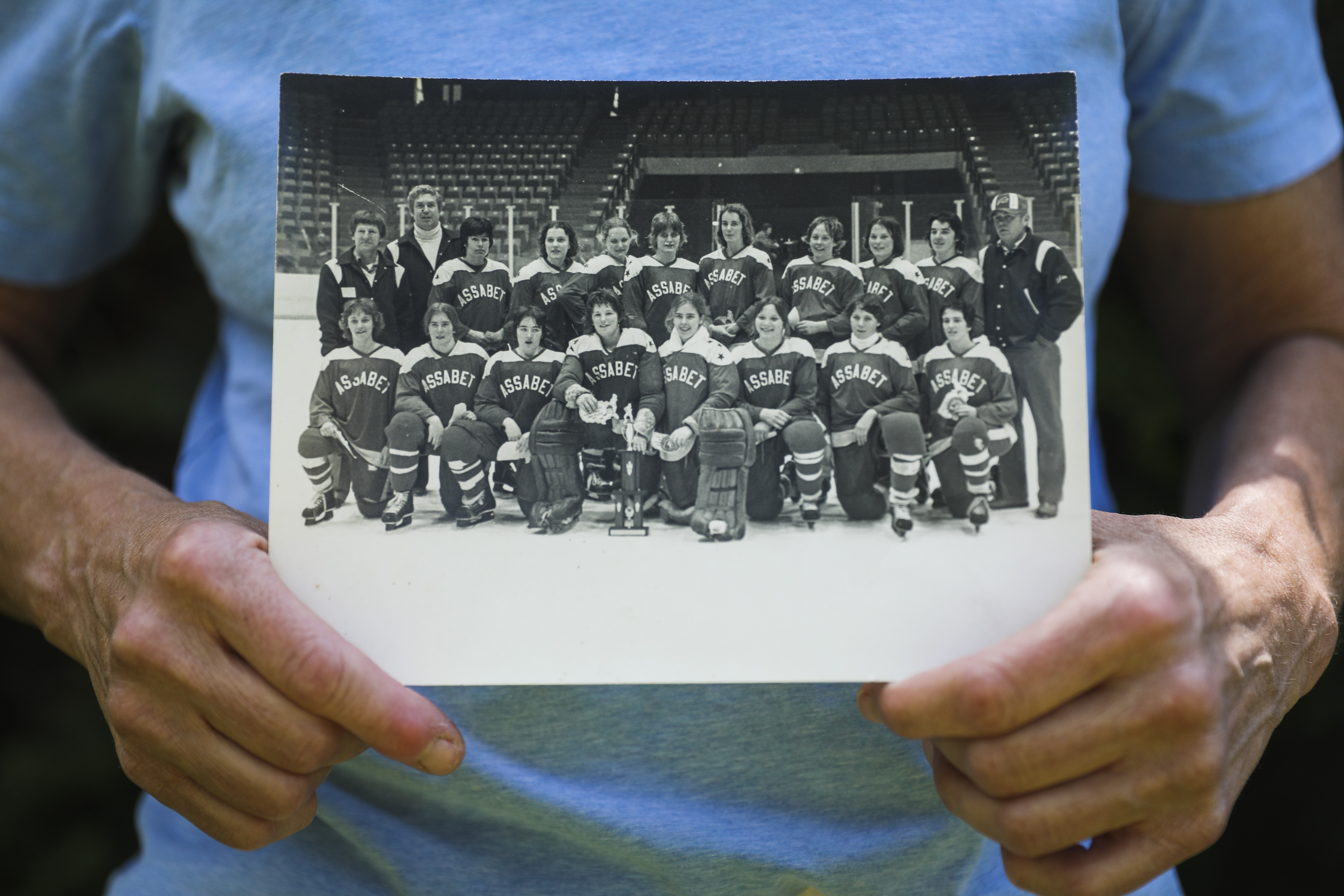 Estey Ticknor holds a photo of the Assabet Valley team. Carl Gray is standing second from left. Ticknor was part of the elite youth hockey program that has helped hundreds of girls receive college scholarship offers. Some have even won Olympic medals.