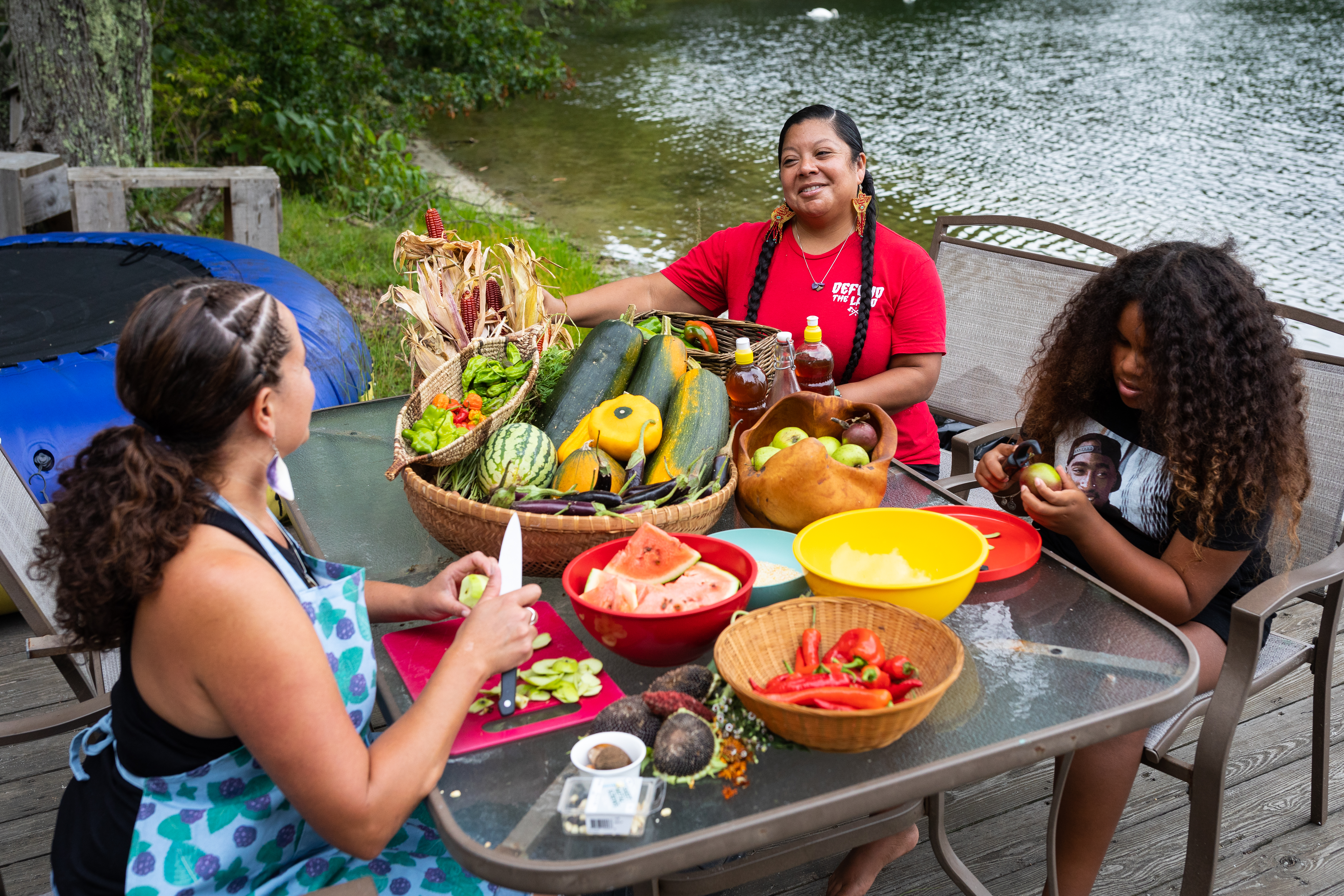 Rachael Devaney speaks with fellow Eastern Woodlands Rematriation Collective member Kristen Wyman while preparing a number of fruits and vegetables in Centerville.