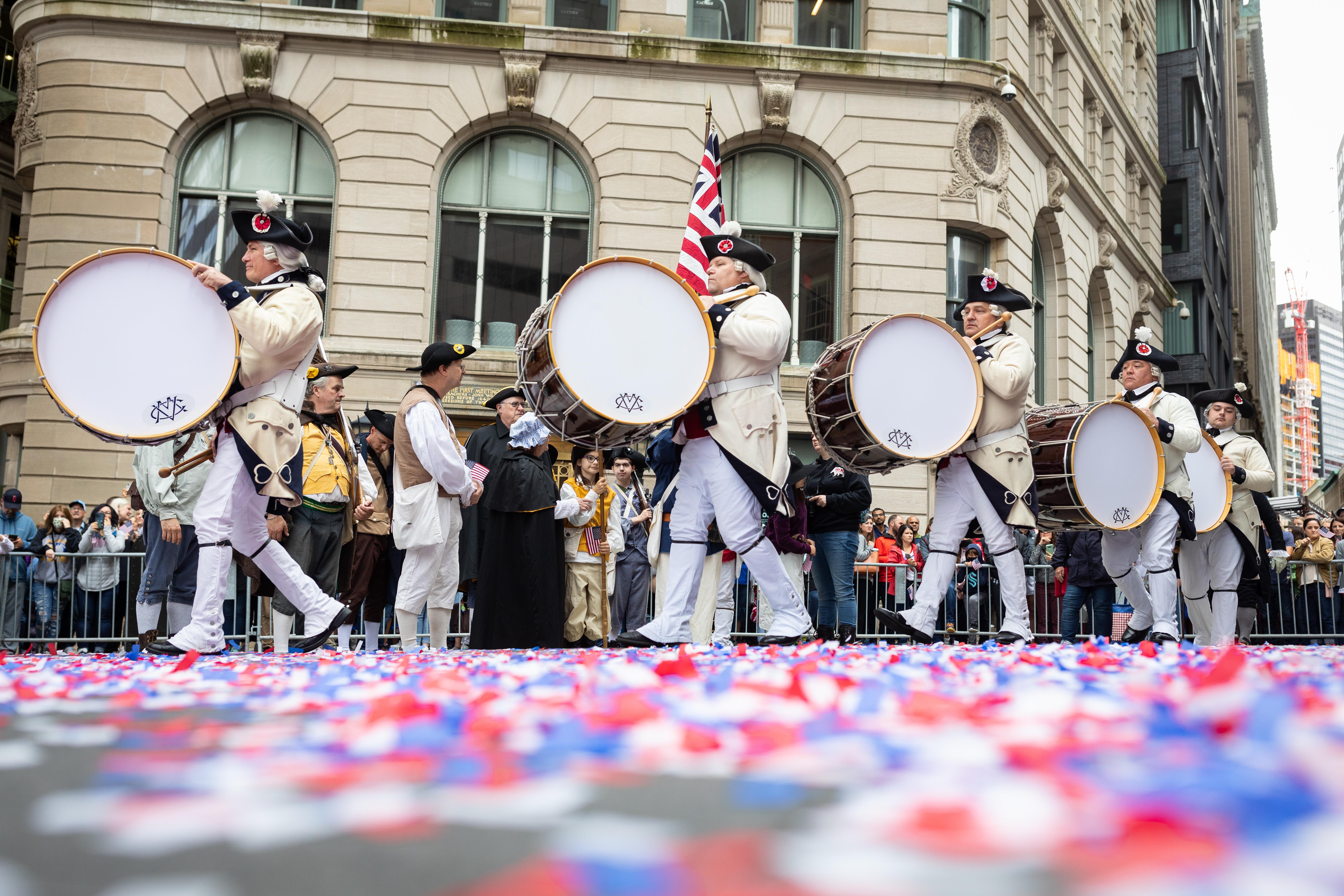 Anggota sukarelawan Middlesex County berbaris dengan drum di atas confetti merah, putih dan biru di dekat Old State House selama parade pada 4 Juli di Boston, MA.