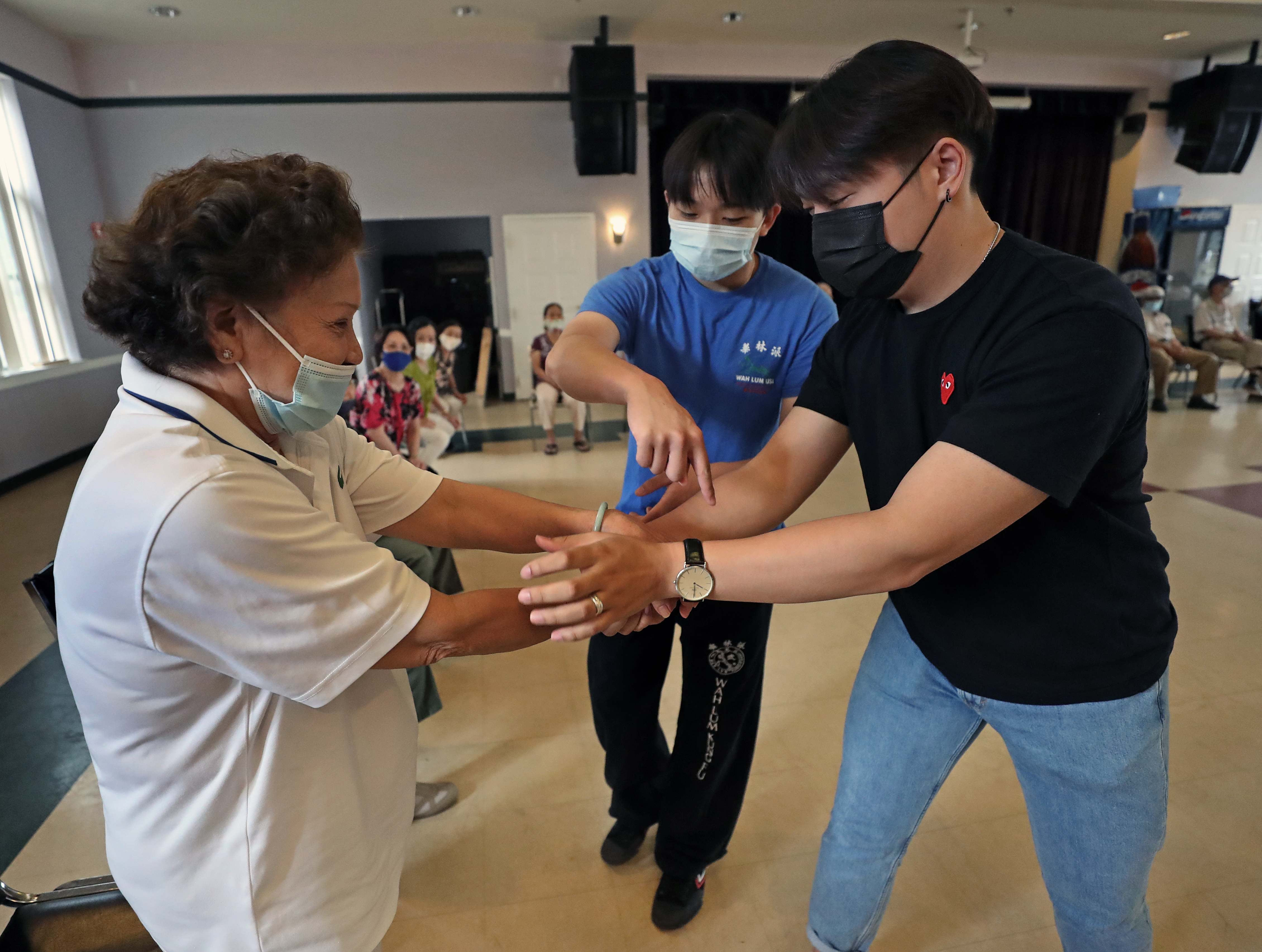 Linh Mat, 88, was shown how to break loose from an assailant by Thomas Tran (center) and Nhan Truong at VietAID.