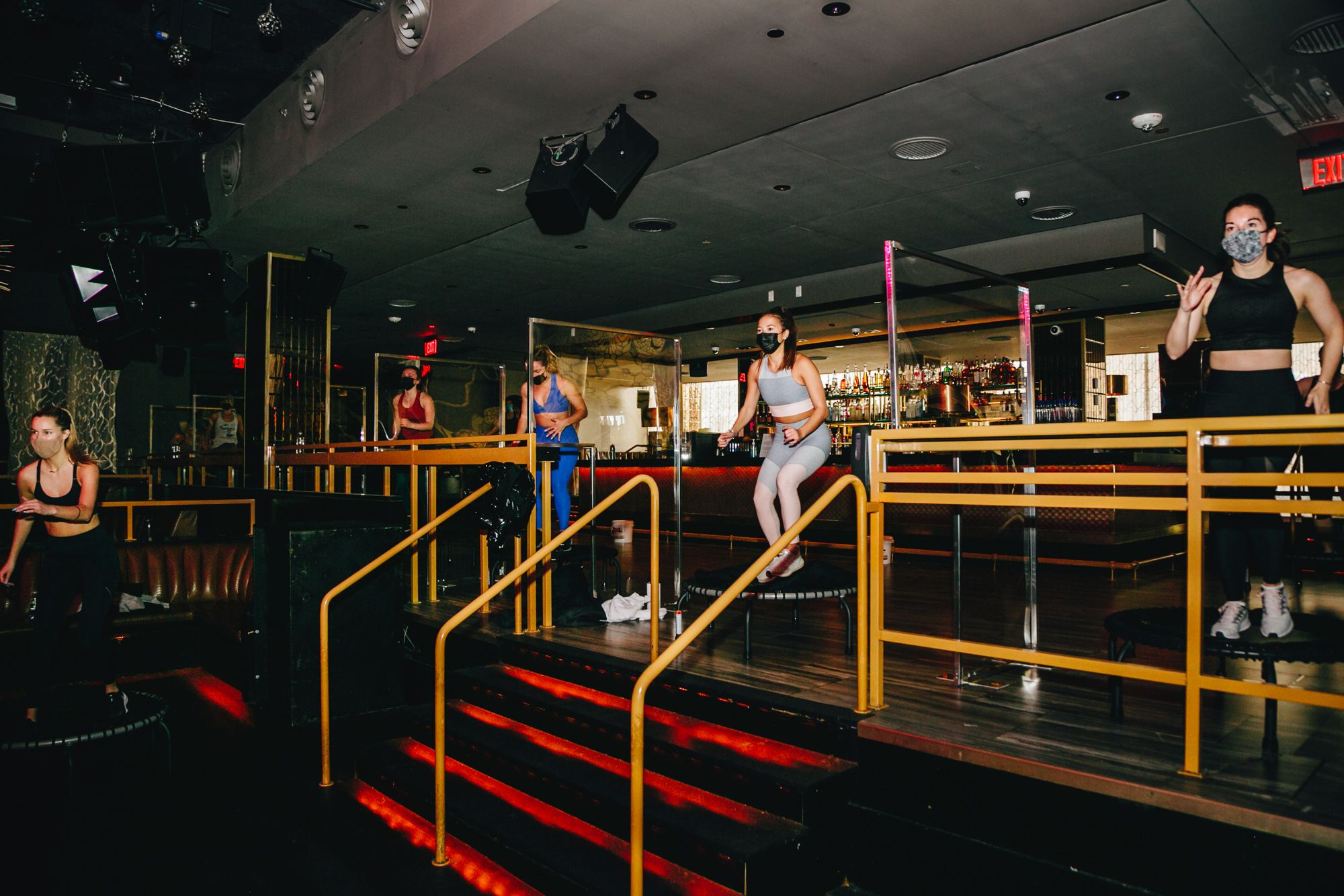Participants in a Barre Groove class jump on trampolines in front of a bar at the Grand in the Seaport District, which remains closed as a nightclub.