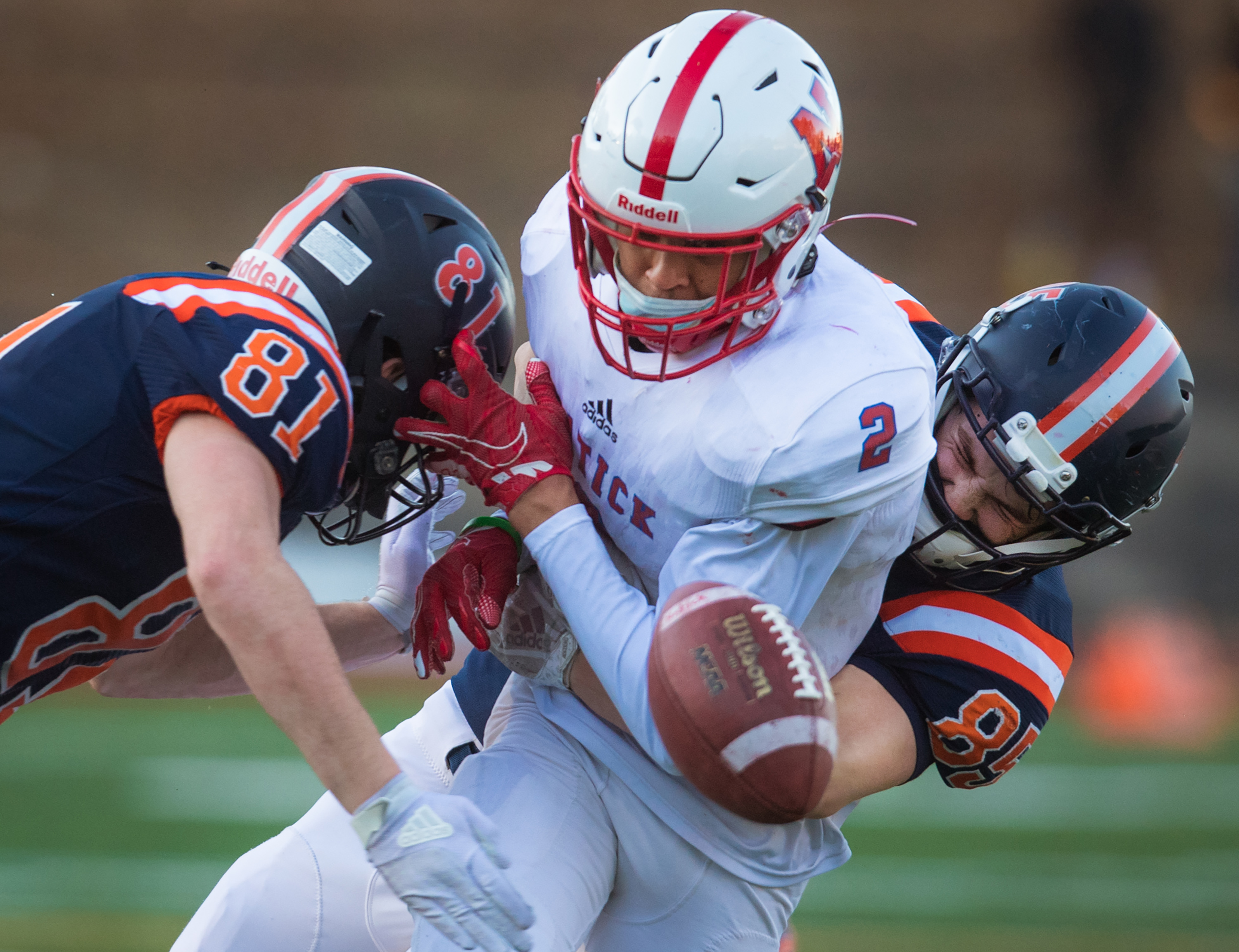 A crunching hit from Walpole's James Maguire (left) and Cole Tashjian separated Natick's Nick Ofodile (2) from the ball in Friday night's Bay State Conference game.
