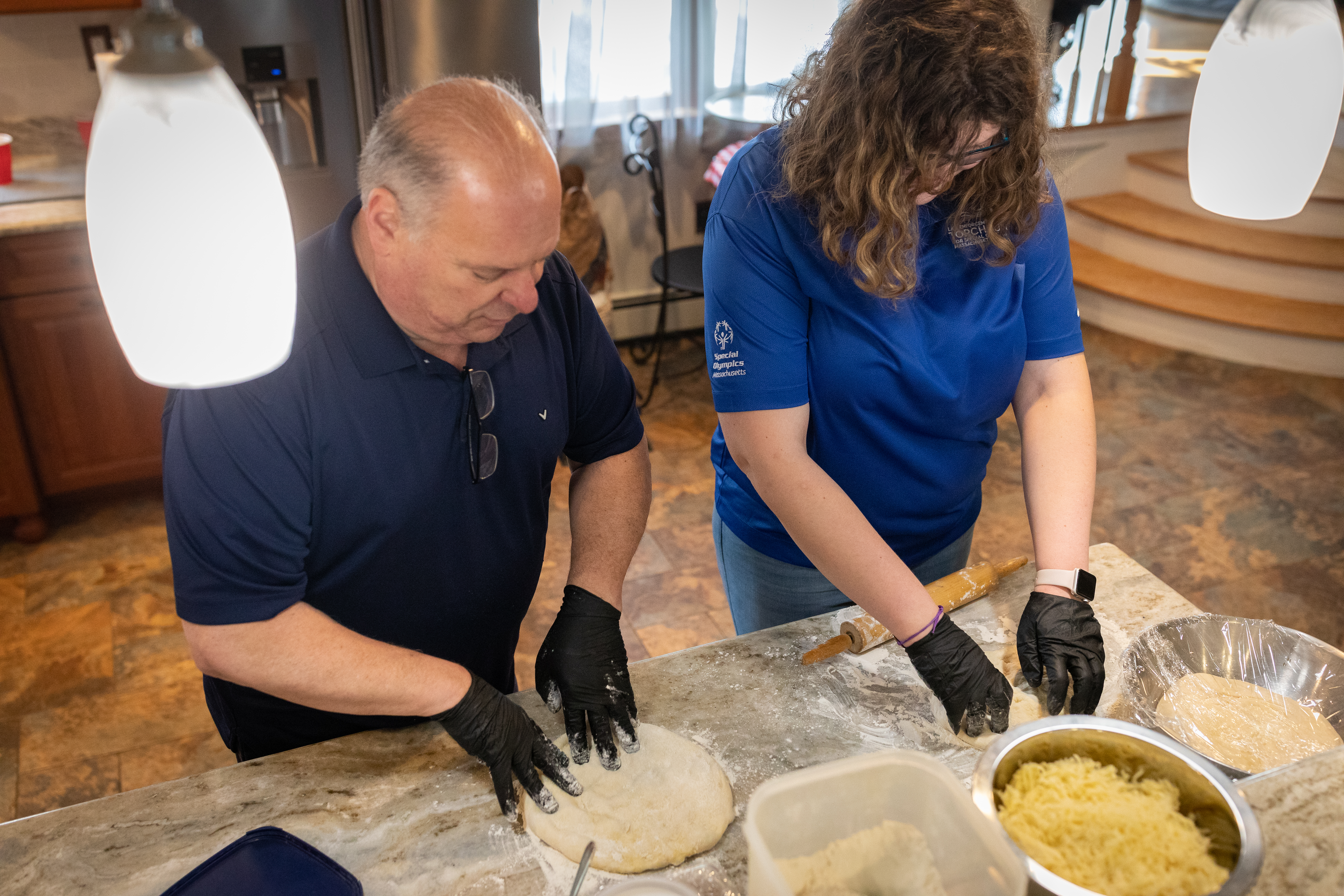 Meghan Colby, a Special Olympics athlete, forms pizza dough into a pie alongside retired Middleton Police Chief Jim DiGianvittorio during a live-streamed pizza cooking tutorial.