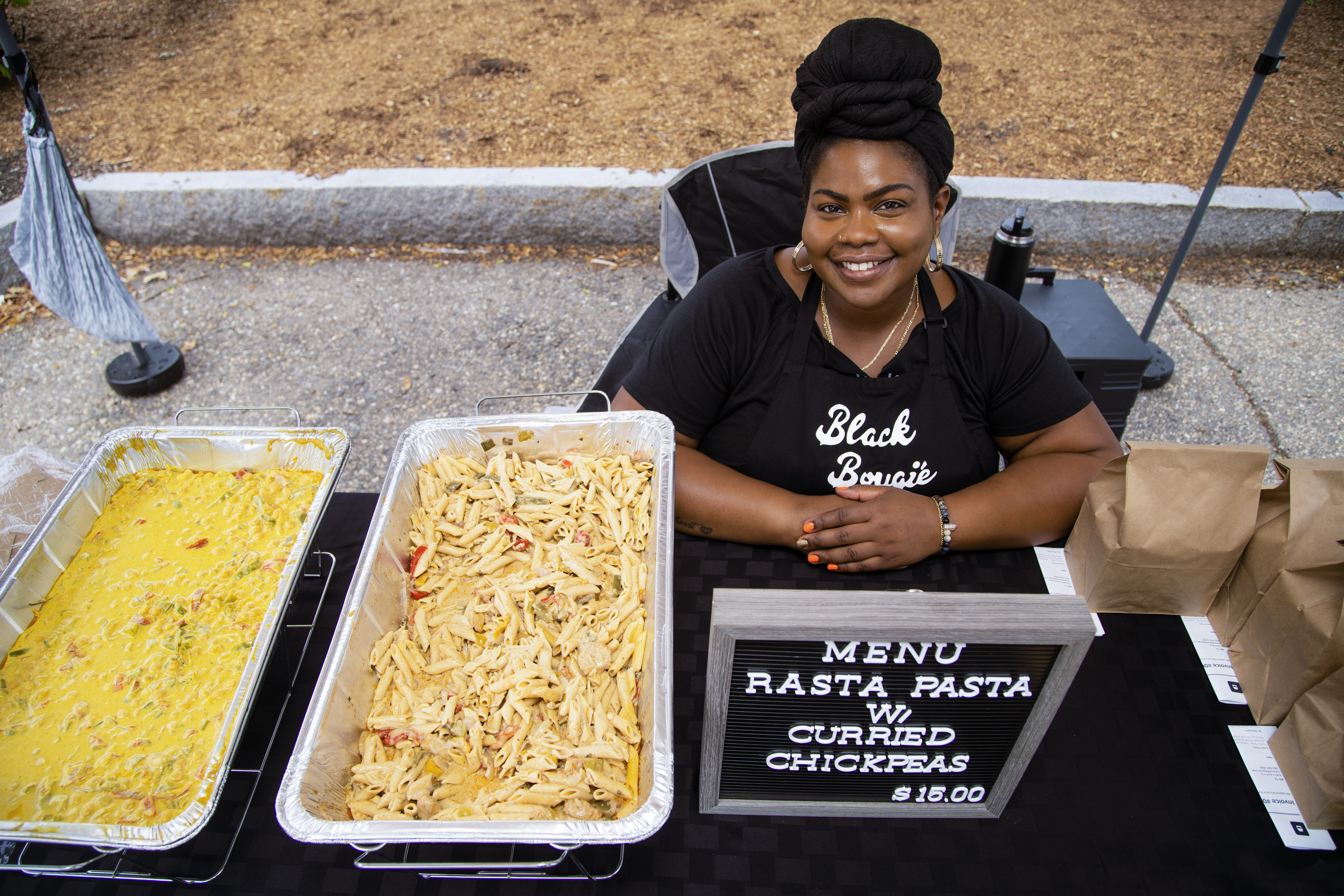 Kedian Dixon of Black Bougié & Vegán sits at her booth at a vegan food market in Dover, N.H., on Sunday.