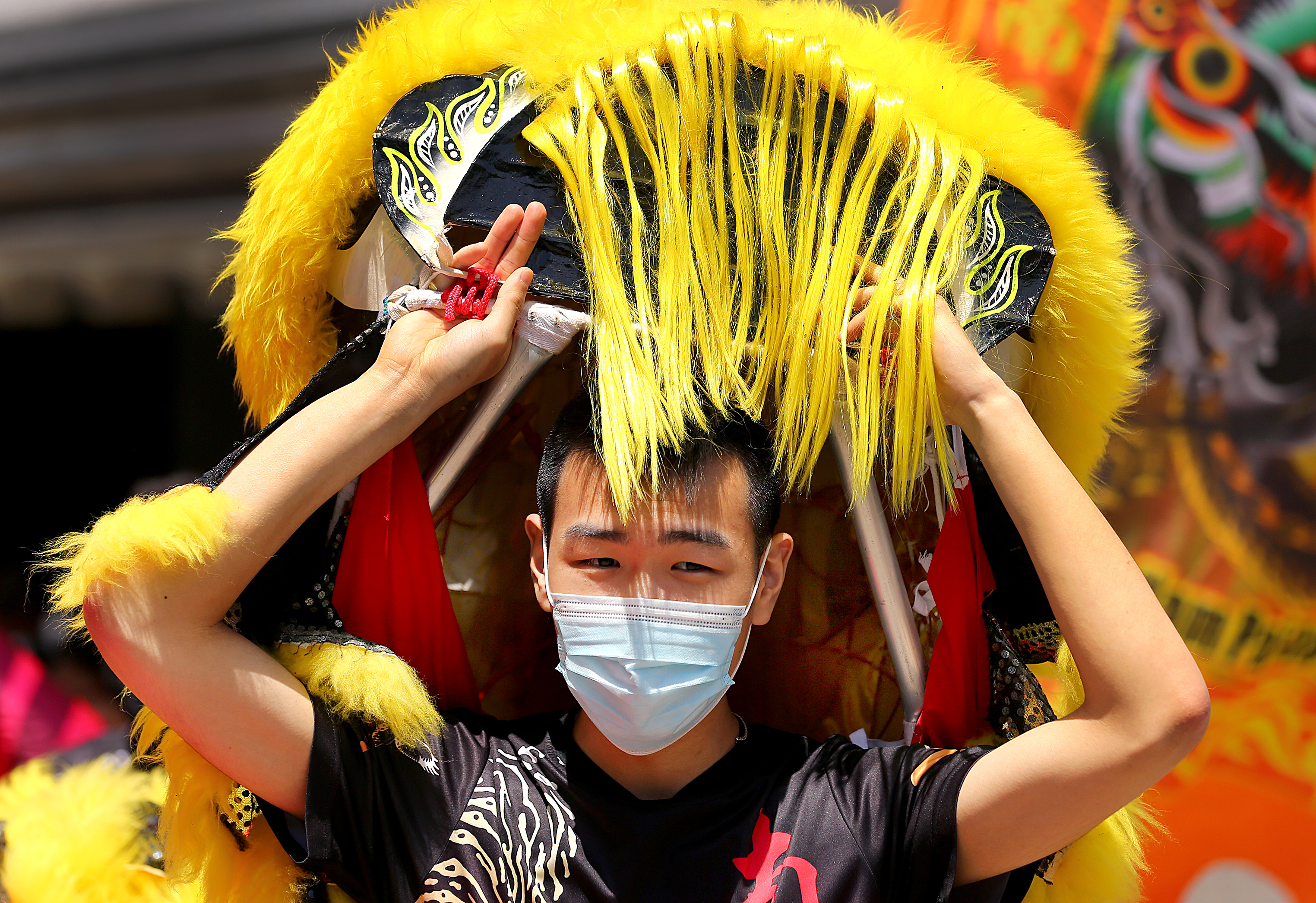 Dancer Henry Yu put on the head section of the lion costume.