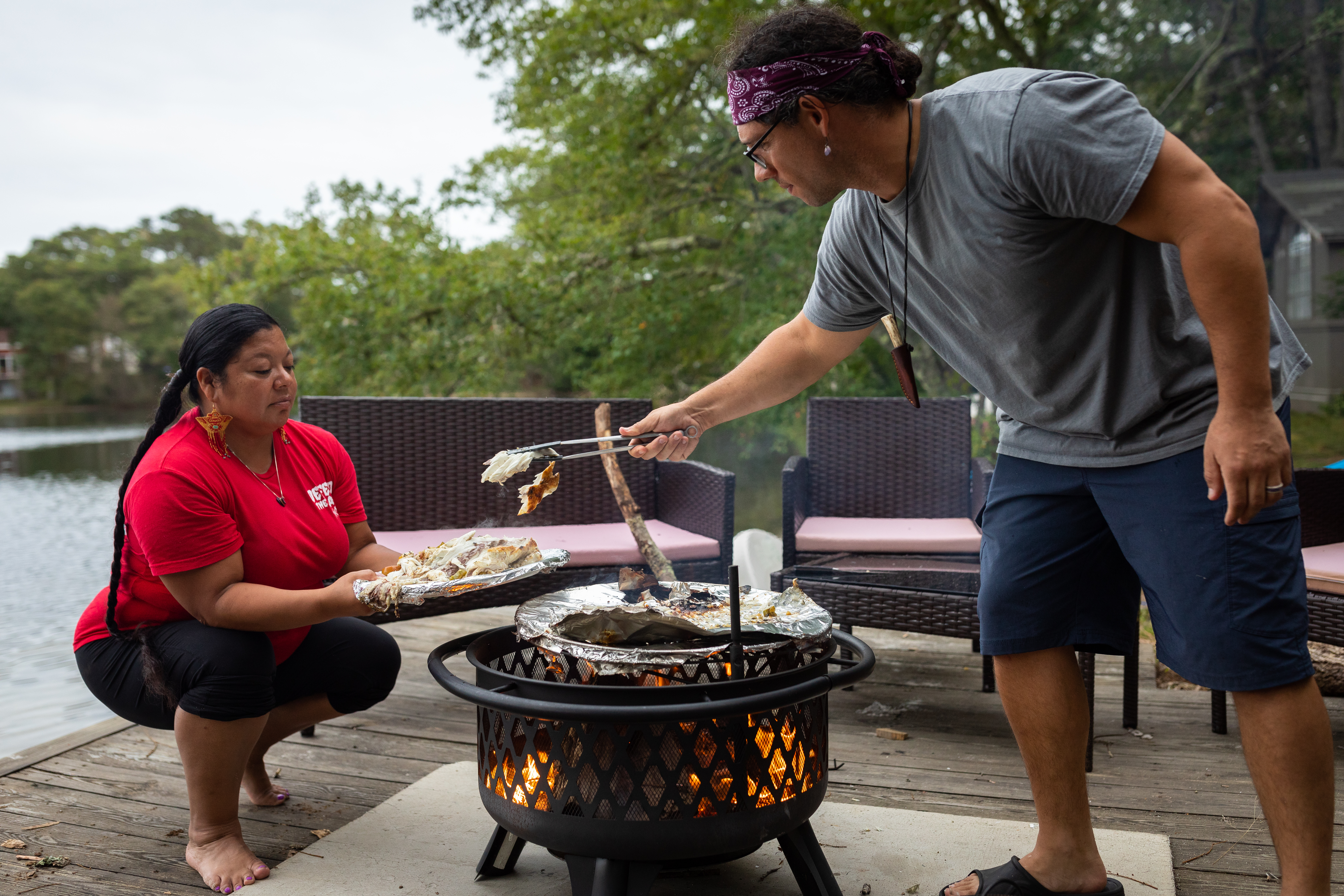 Marcus Hendricks, a member of the Eastern Woodlands Rematriation Collective, passes pieces of cooked striped bass to Rachael Devaney in Centerville.