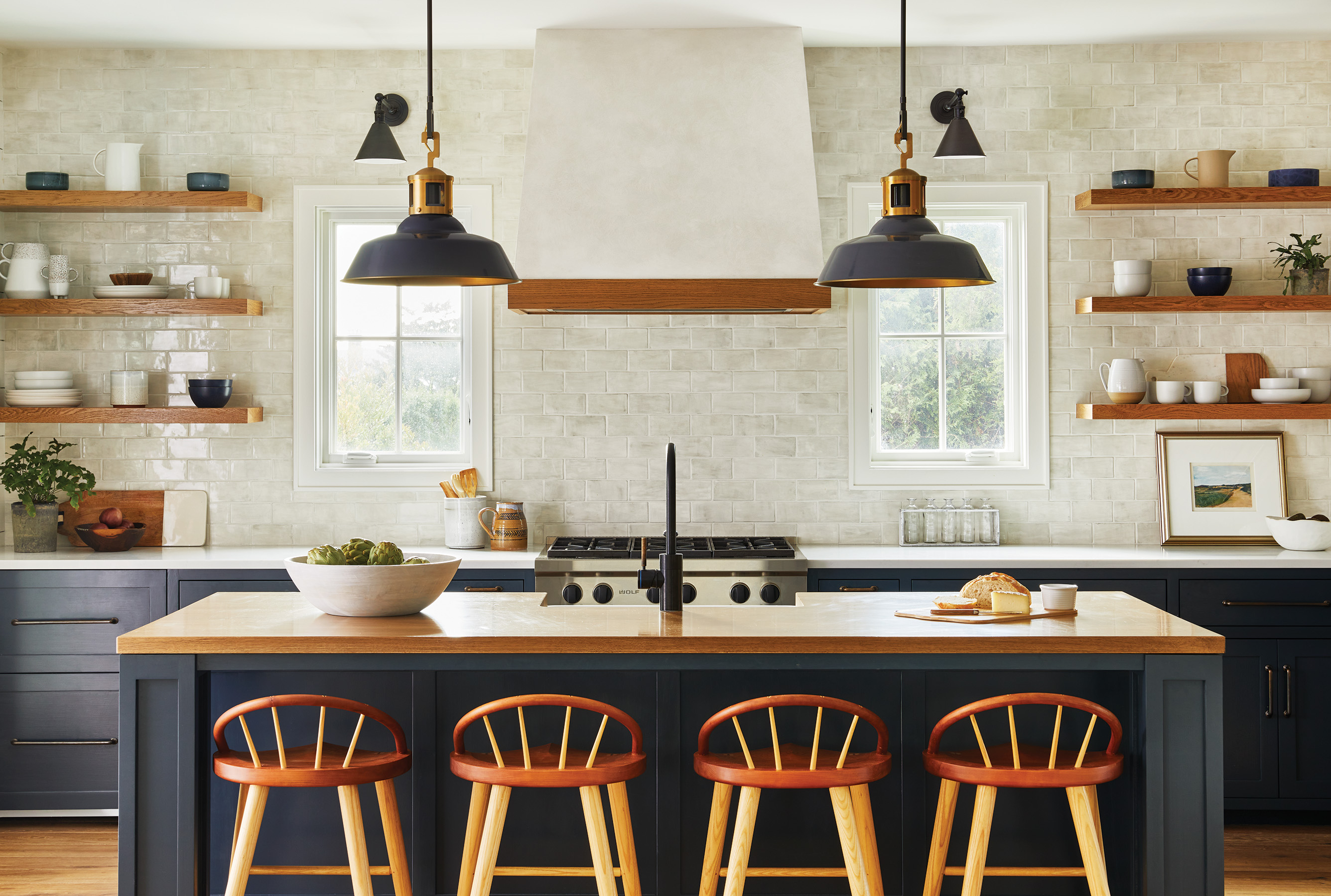Birch and ash stools from New England furniture maker Thos.  Moser lines the island and the Urban Electric Co. pendants hang above it.