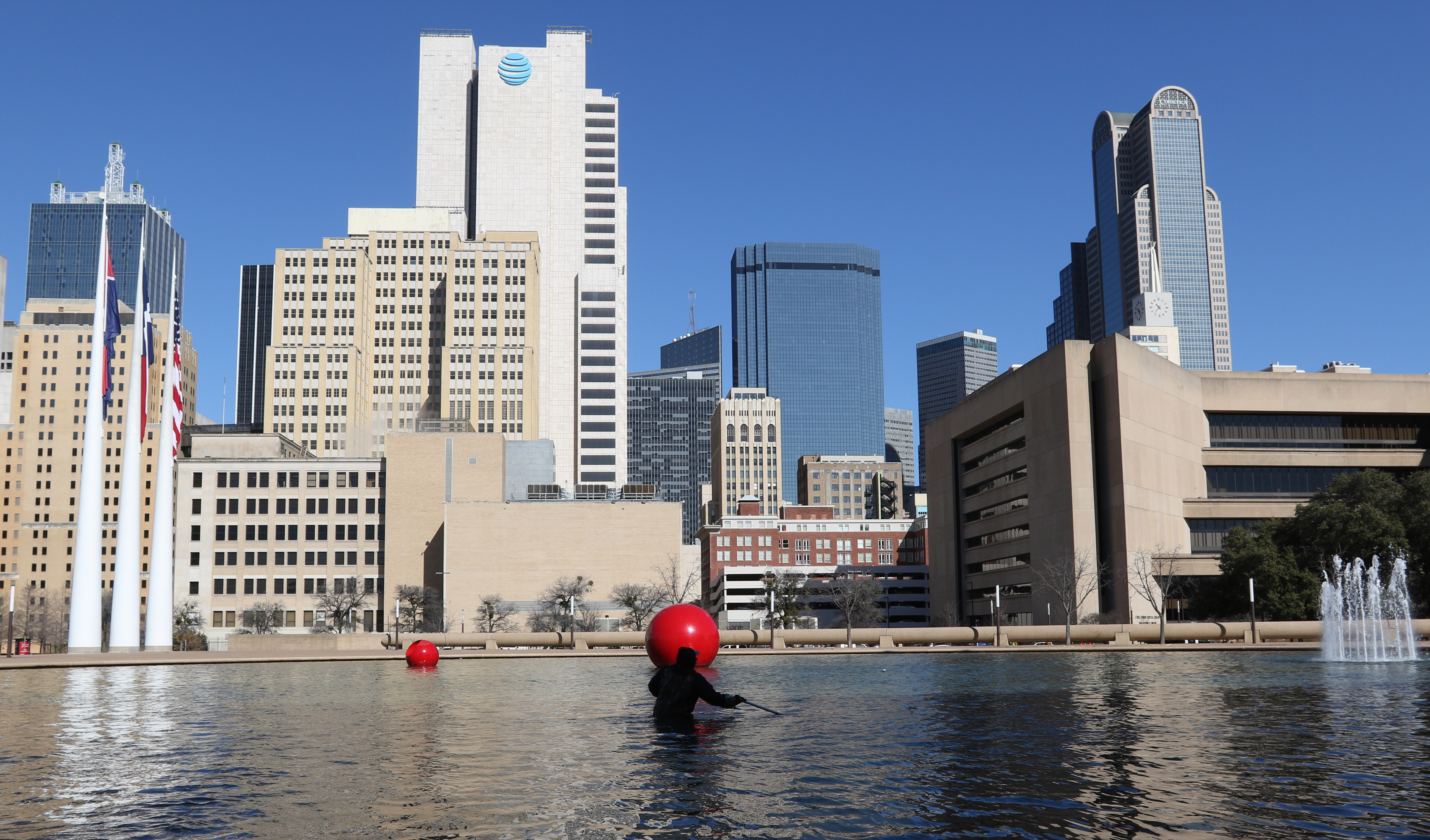 A city of Dallas employee cleans the reflecting pool at Dallas City Hall in downtown Dallas, Feb. 12, 2019. (Benjamin Robinson/The Dallas Morning News)