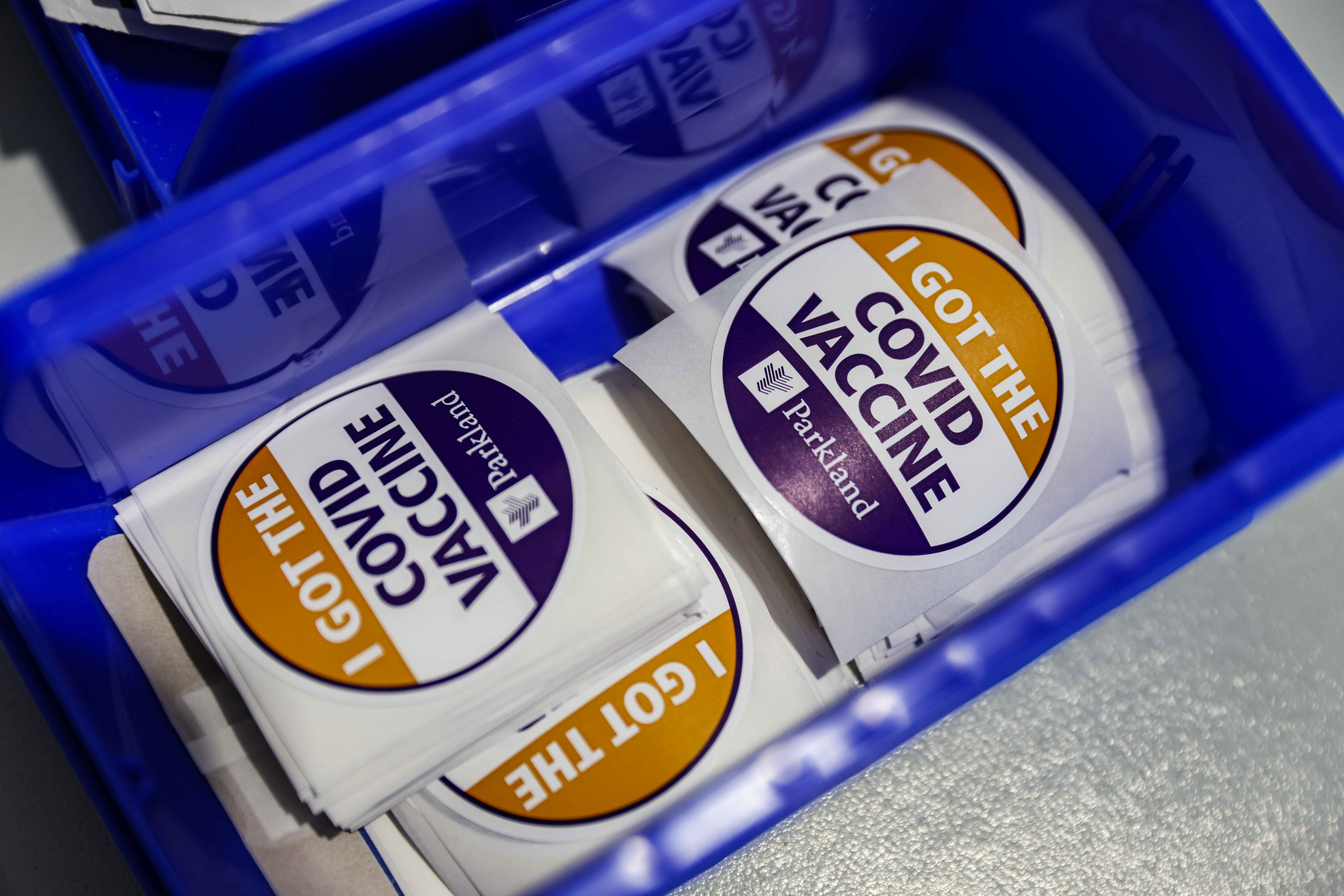 COVID vaccine stickers where the Pfizer-BioNTech COVID-19 vaccine is administed at Ellis Davis Fieldhouse, a Parkland Hospital testing and vaccine location, in Dallas on March 3, 2021. (Lola Gomez/The Dallas Morning News)