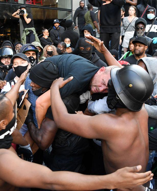 El manifestante negro Patrick Hutchinson retira en sus hombros a otro blanco que había quedado lastimado tras los enfrentamientos.