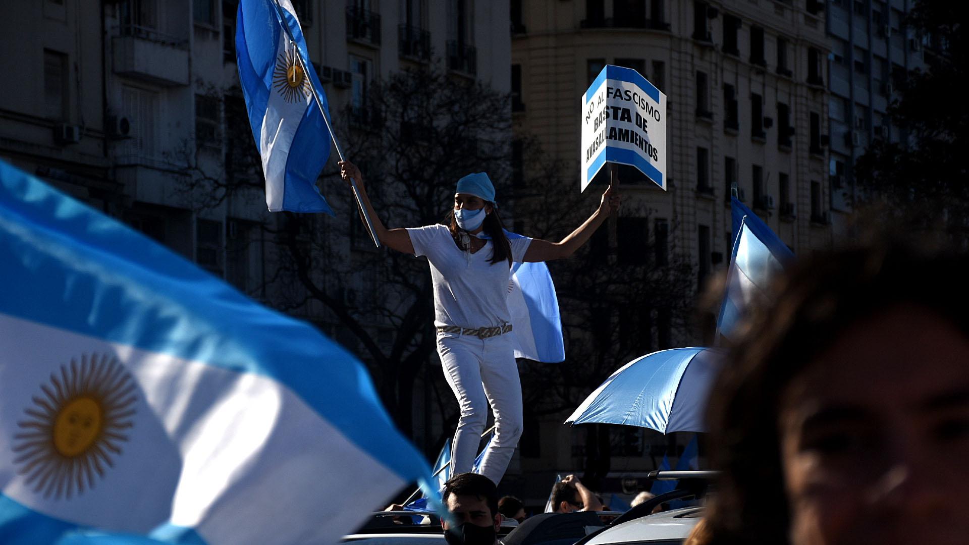 Una mujer protestó con una bandera argentina arriba del techo de un auto