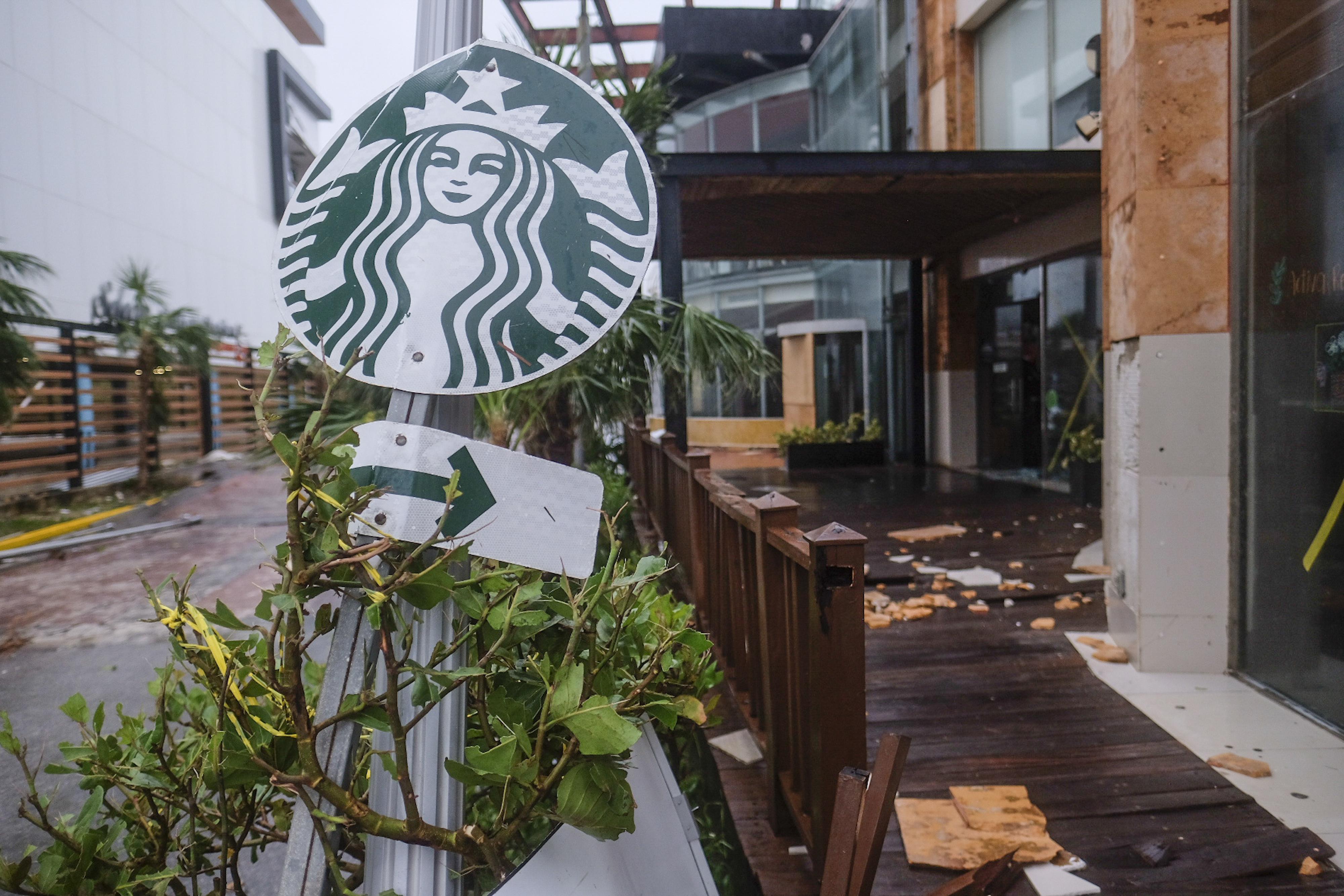 Un letrero de una cafetería Starbucks lleva de regreso después de ser empujado por los vientos del huracán Delta en Cancún, México, el miércoles 7 de octubre de 2020.