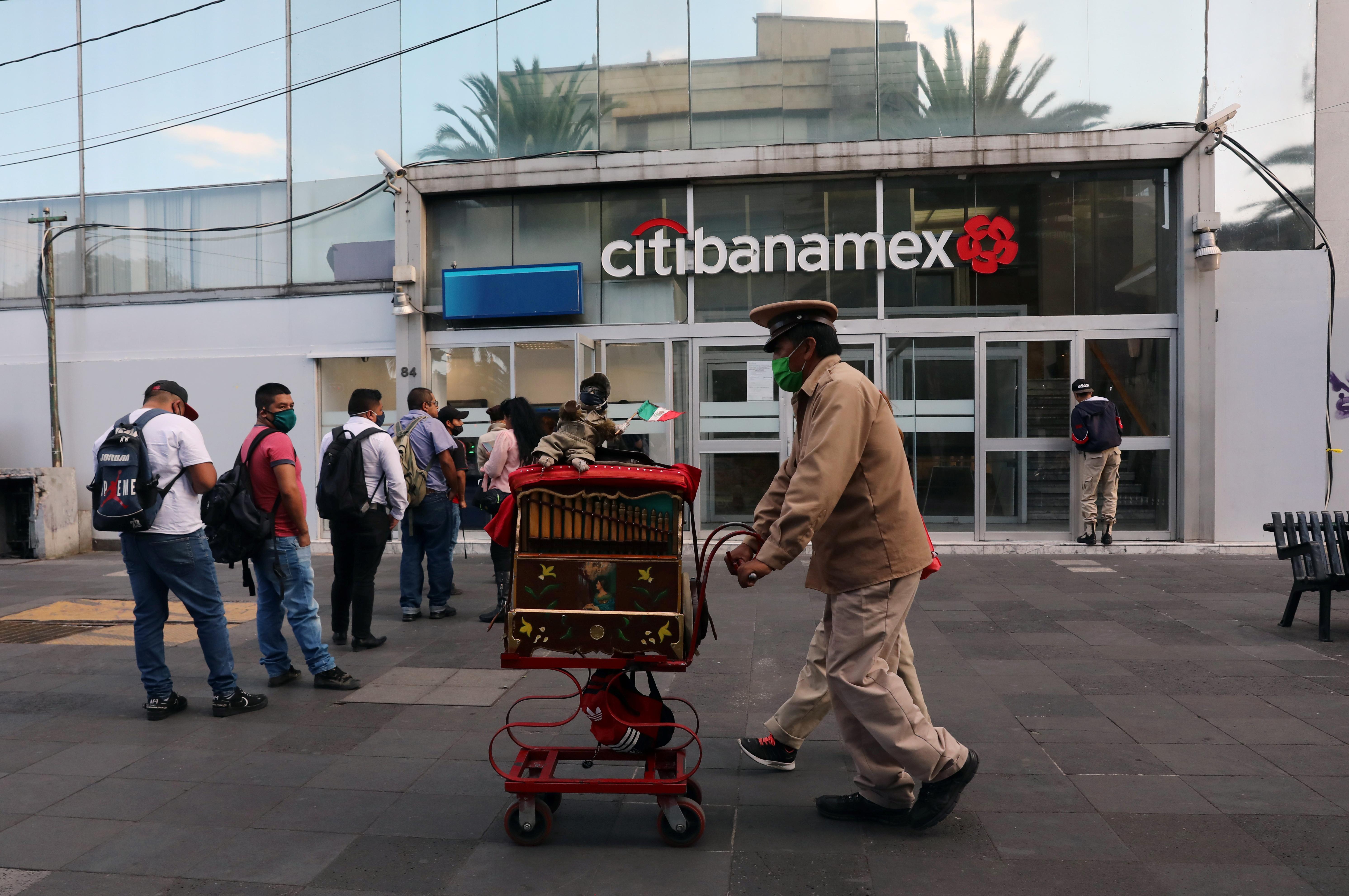 Un músico empuja un organillero a lo largo de una acera cuando el alcalde de la Ciudad de México dijo el viernes que la capital mexicana levantará las restricciones sobre el tráfico de automóviles y el transporte público. Ciudad de México, México, 12 de junio de 2020. Foto: Reuters.