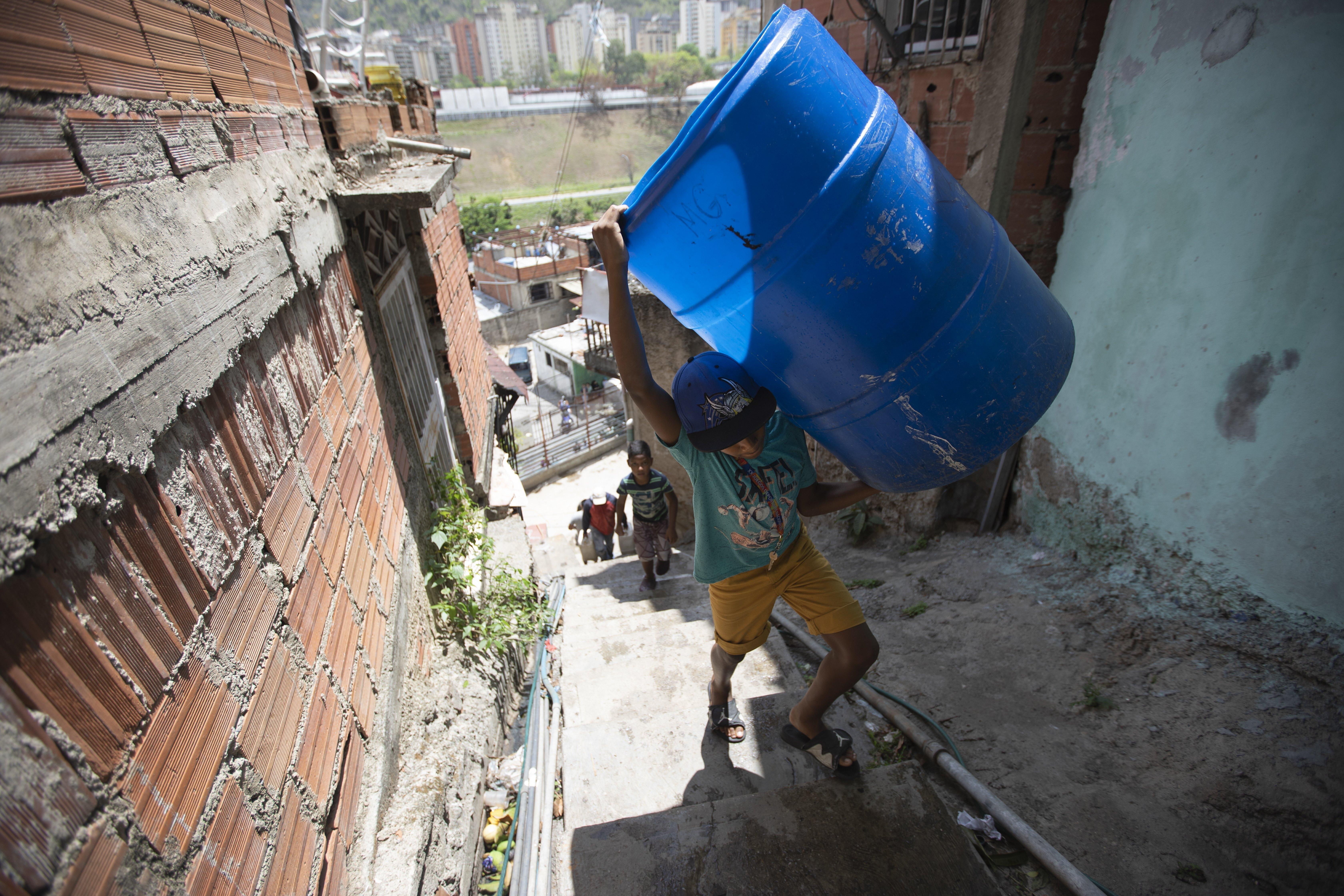 Un niño sube unas escaleras cargado con dos recipientes vacíos que llenará con el agua suministrada por un camión cisterna del gobierno, en el vecindario de Petare, en Caracas, Venezuela, el 15 de junio de 2020. El colapso económico de Venezuela ha dejado a la mayoría de los hogares sin un suministro de agua corriente confiable. (AP Foto/Ariana Cubillos)