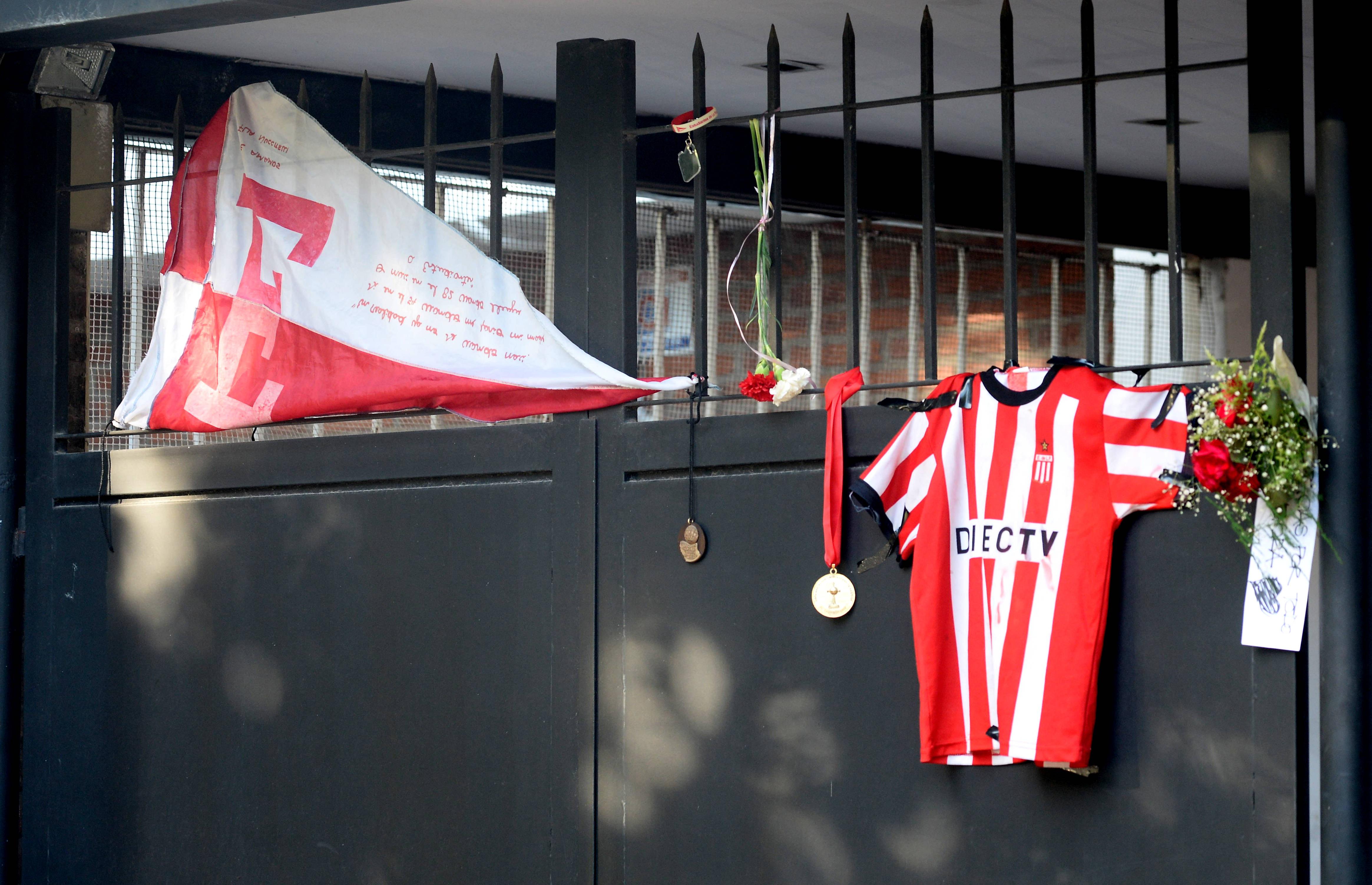 La bandera de Estudiantes de La Plata, camiseta del León y medallas, colgadas en el portón de la casa de Sabella