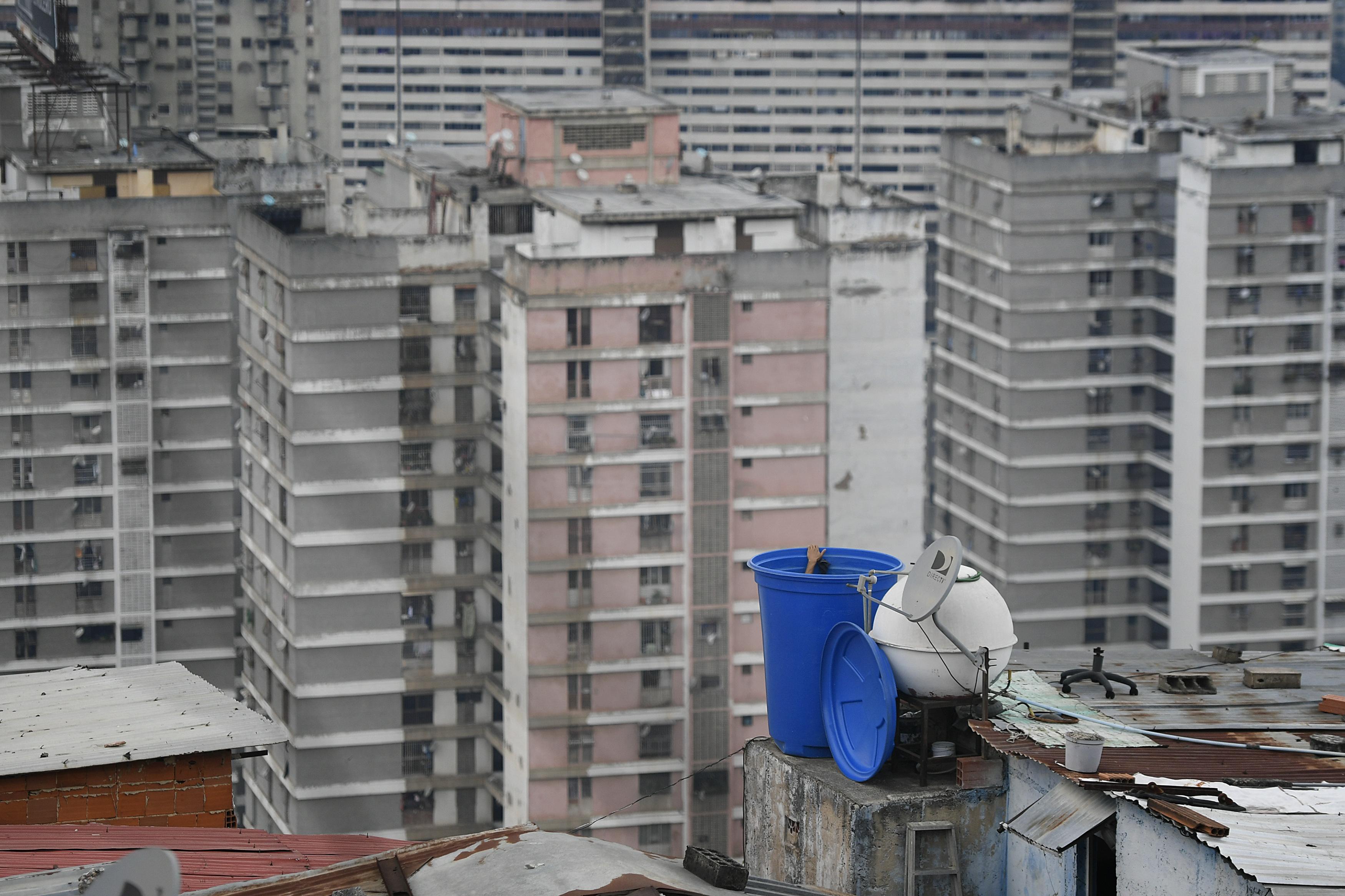 Un hombre limpia el interior de un contenedor de agua situado sobre el tejado de su casa en el vecindario de San Agustín, en Caracas, Venezuela, el 17 de mayo de 2020. La escasez de agua sigue agravándose en Venezuela en un momento en que la amenaza del coronavirus hace que lavarse las manos sea aún más crítico. (AP Foto/Matías Delacroix)