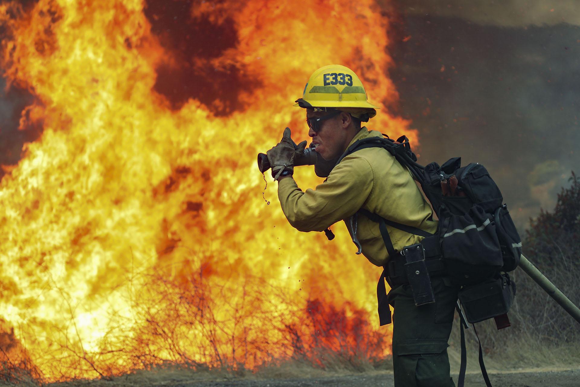 A diferencia de la primera oleada, cuando los fuegos se concentraron en el norte del estado, esta vez la peor parte se la están llevando el centro y el sur, con dos grandes fuegos que queman cerca de Los Angeles y San Diego, y un tercero declarado en la Sierra Nevada. (SANDY HUFFAKER / AFP)