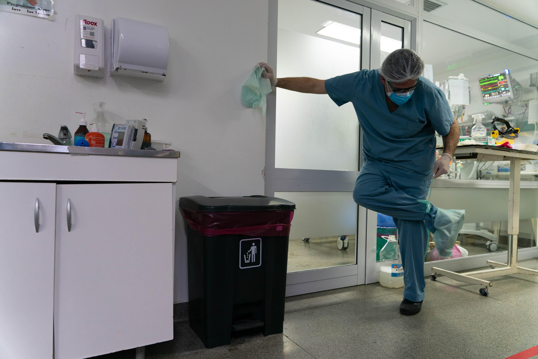 Leandro Tumino se retira de una habitación y se saca todo el equipamiento de seguridad.