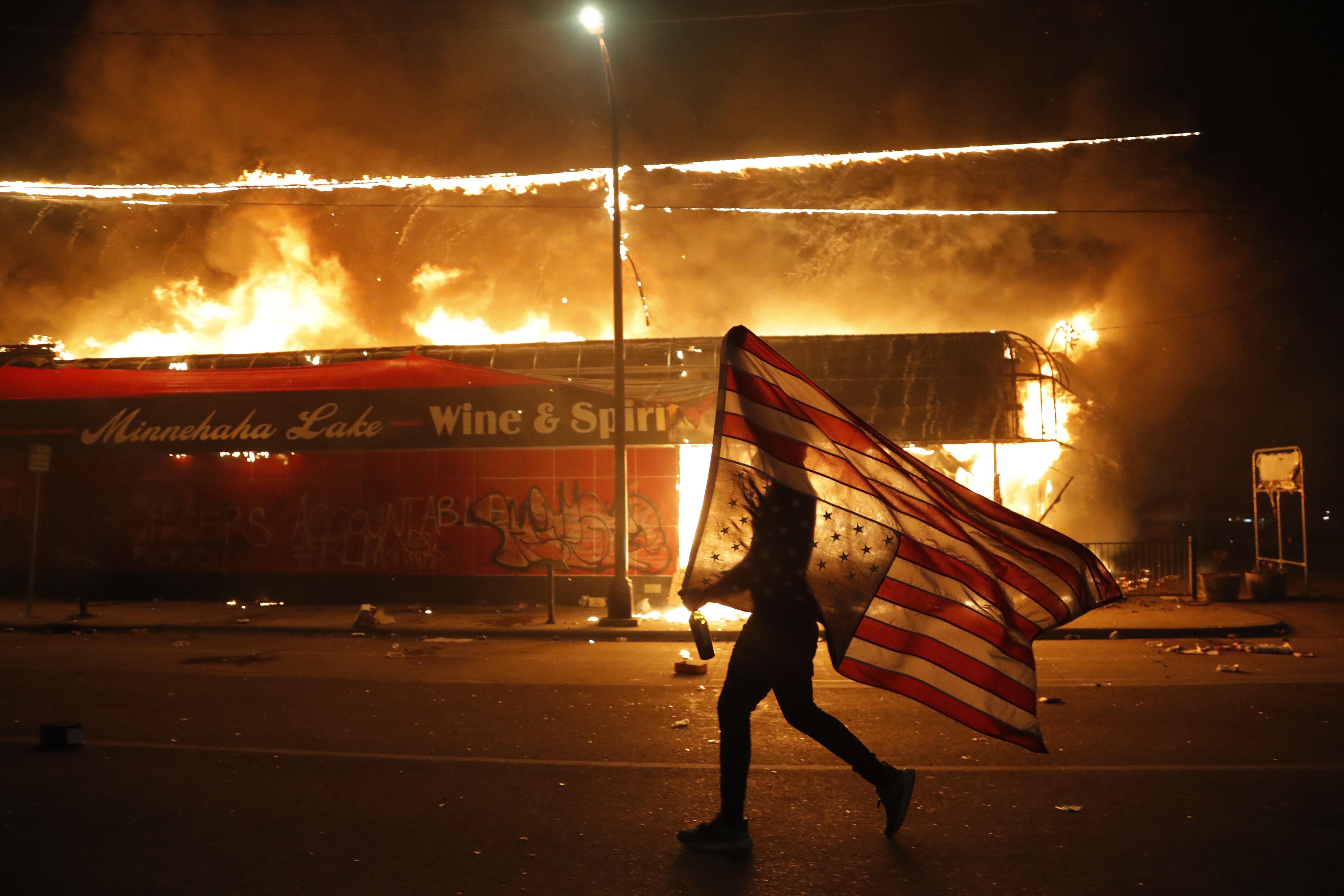 Un manifestante lleva una bandera de EE.UU. al revés junto a un edificio en llamas el jueves 28 de mayo de 2020, en Minneapolis (Foto AP/Julio Cortez)
