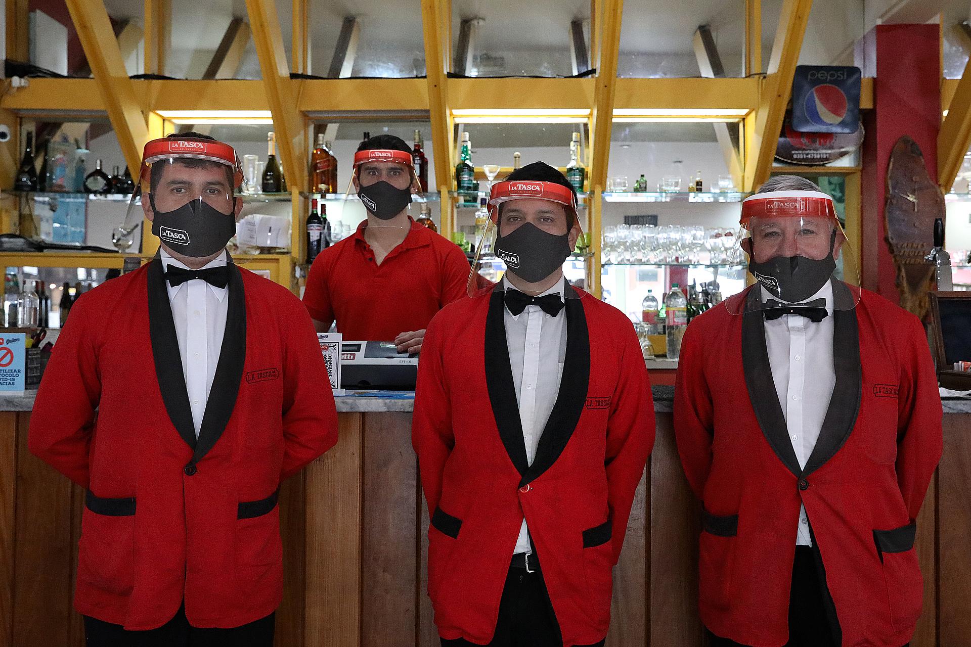 A su tradicional uniforme de saco rojo y moño negro, los camareros de