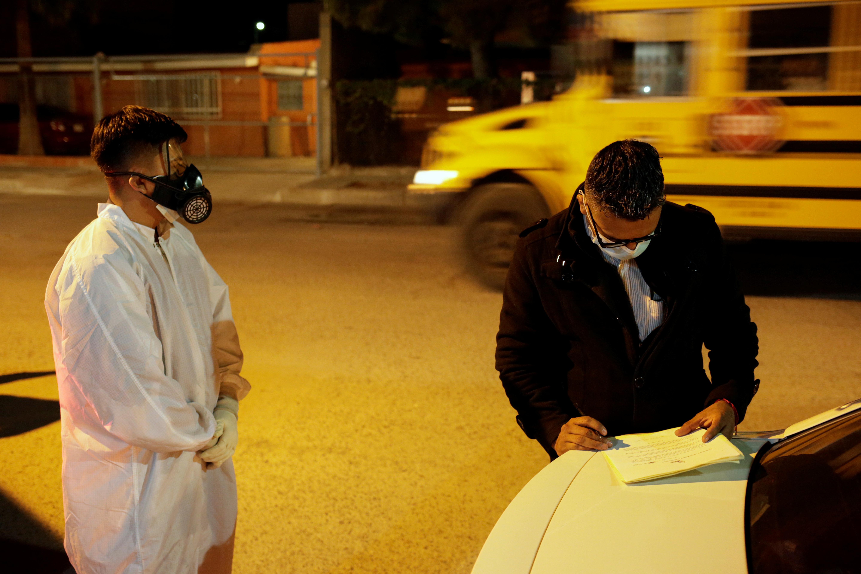 Un hombre firma un documento después de que los empleados de la funeraria Ríos trasladaron el cuerpo de un miembro de la familia, que murió por coronavirus (COVID-19), a una funeraria en Ciudad Juárez, México, el 23 de octubre de 2020.