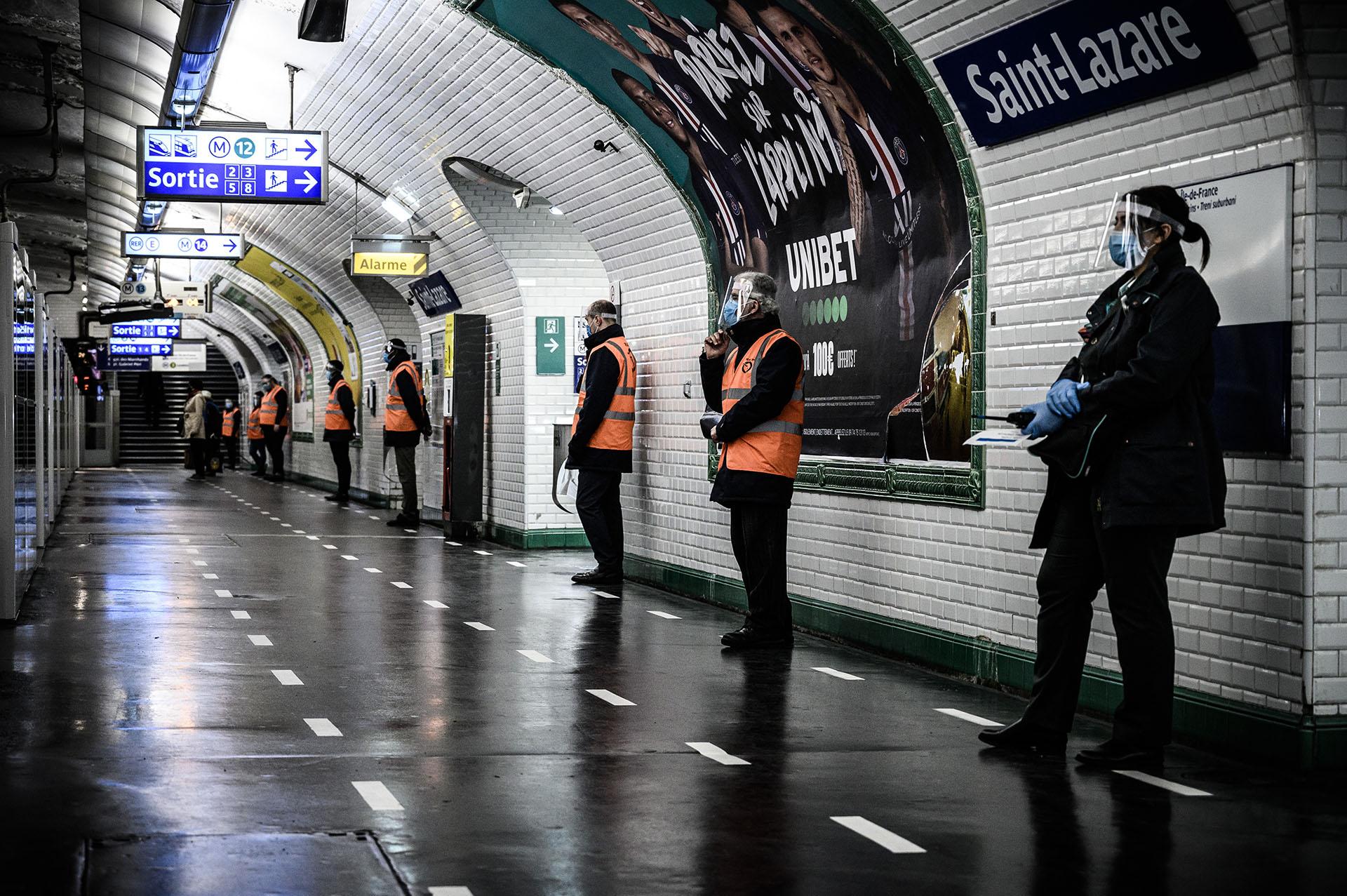 Empleados de la Autoridad Parisina del Transporte controlan que se mantenga la distancia social en la estación Saint-Lazare del metro de la capital francesa.