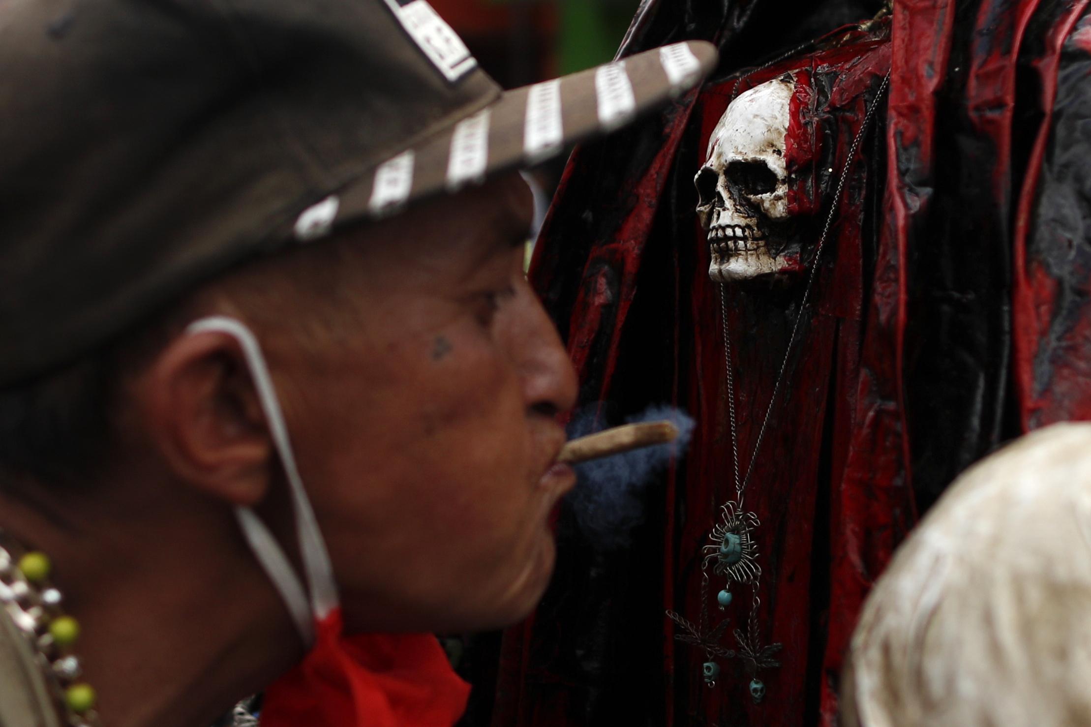 Un hombre sopla humo de marihuana, para limpiarse, sobre el cofre de una Santa Muerte. (Foto: AP / Rebecca Blackwell)