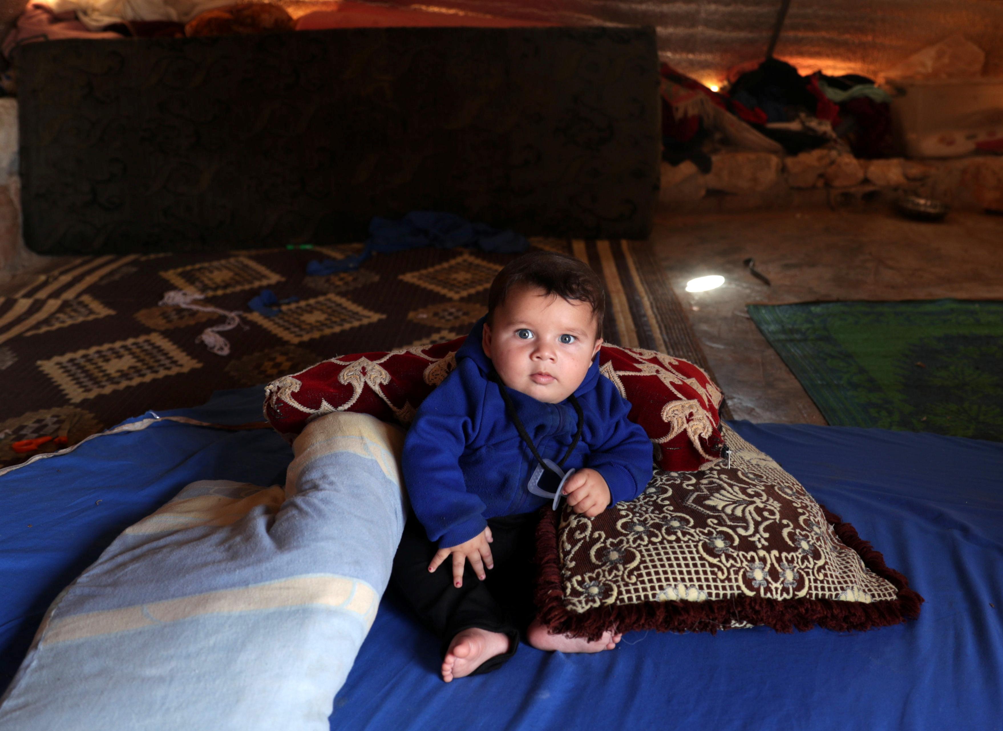 Abdul Rahman al-Fares, un bebé de 4 meses apoyado sobre almohadas sobre una manta azul en la tienda de su familia. El sábado fue el el Día Mundial de los Refugiados, que fue el sábado. (REUTERS/Khalil Ashawi)