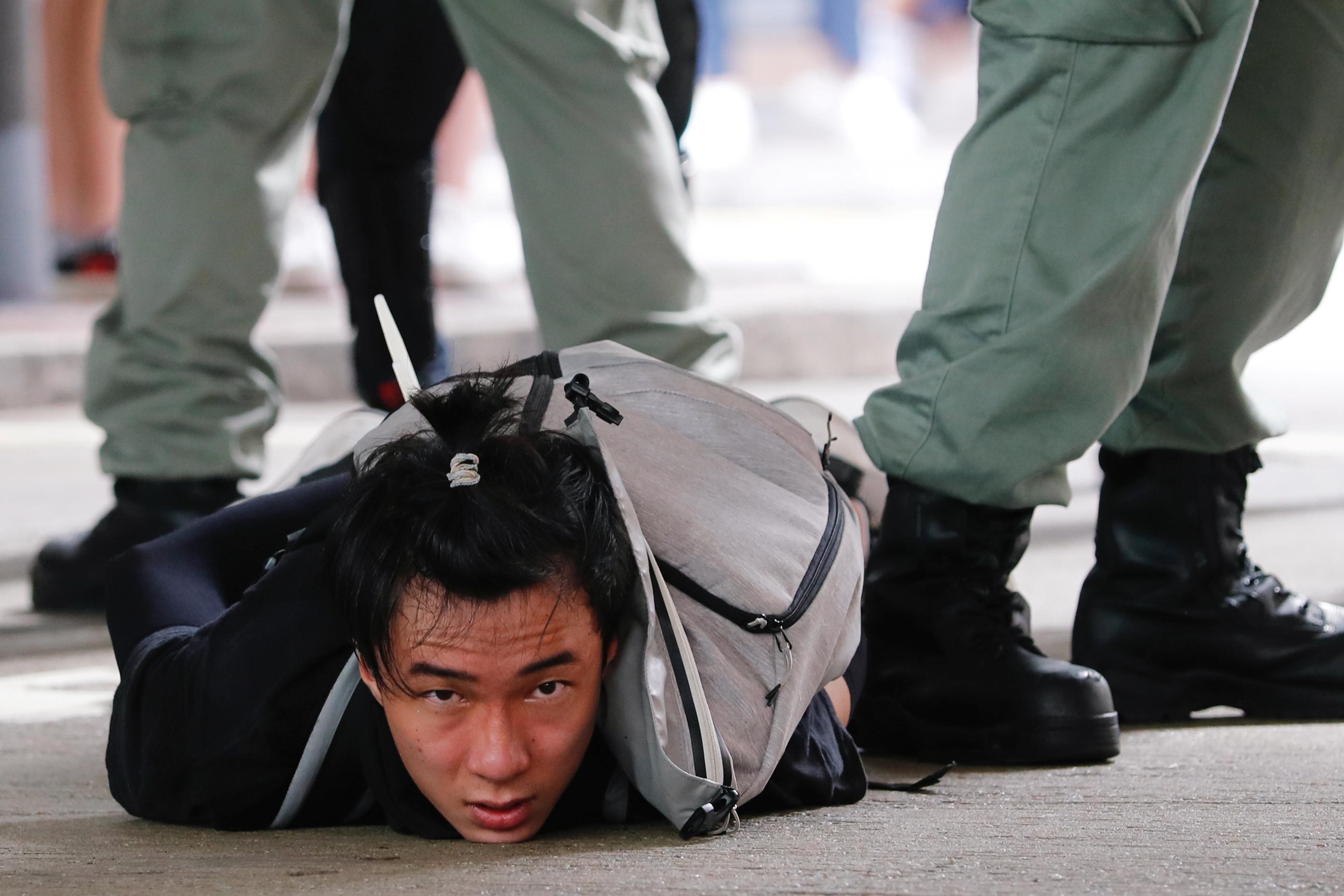 Un manifestante en el suelo, detenido por la policía de Hong Kong
