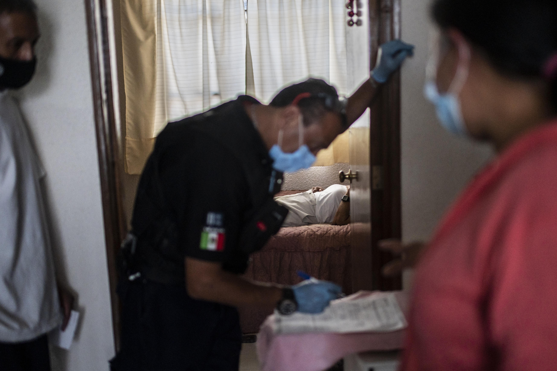 El paramédico Jorge Lino, de 52 años, examina a un hombre con síntomas de COVID-19, en Ciudad Nezahualcóyotl, Estado de México, México, el 21 de junio de 2020 durante la nueva pandemia de coronavirus. (Foto por Pedro PARDO / AFP)