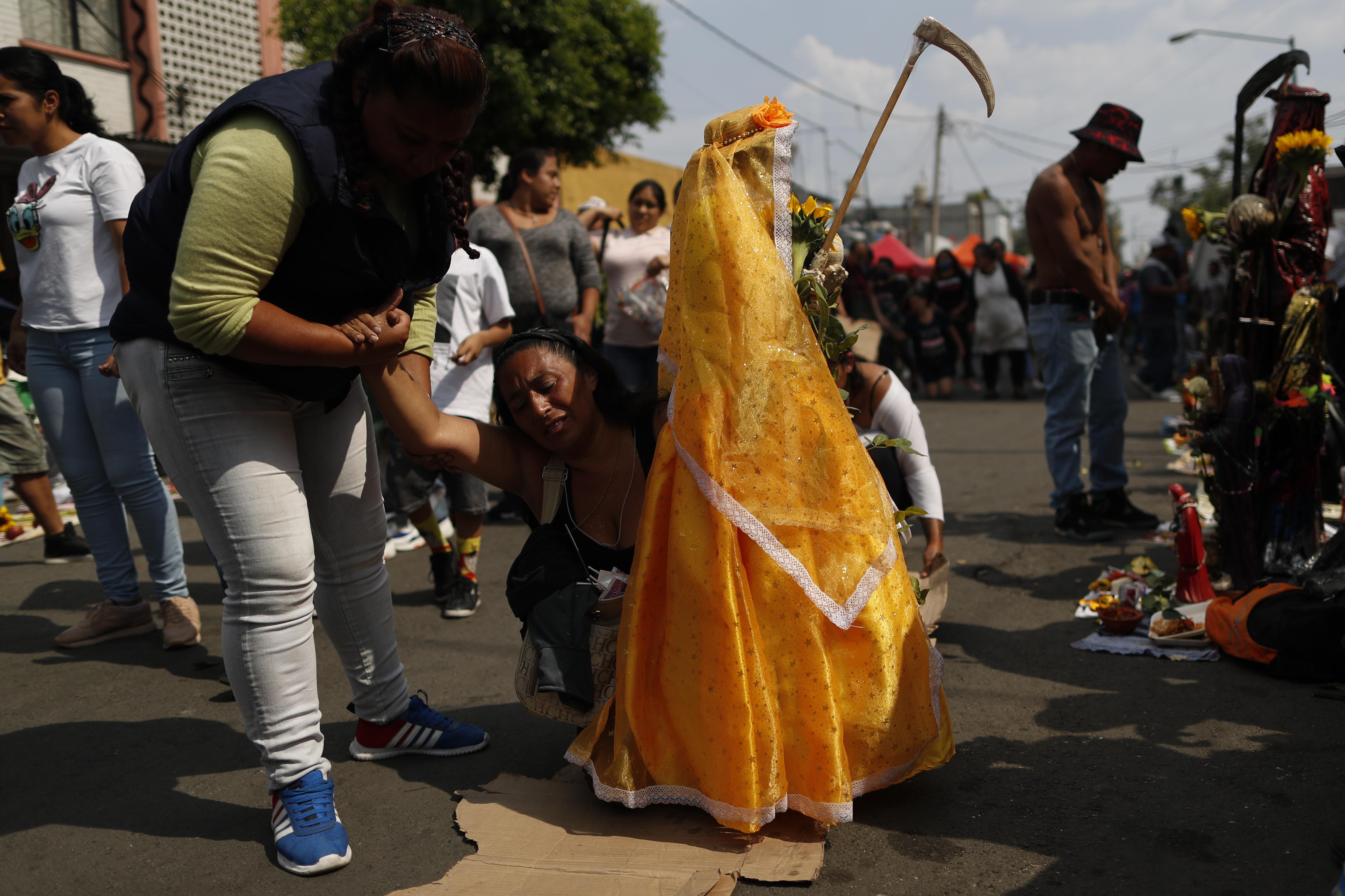 Una amiga ayuda a Victoria Moreno, de 43 años, quien lucha por llegar de rodillas al altar de la Santa Muerte, una promesa que Moreno había hecho al pedirle a la santa que ayudara a salvar a su hija que sufría de apendicitis. (Foto: AP / Rebecca Blackwell)